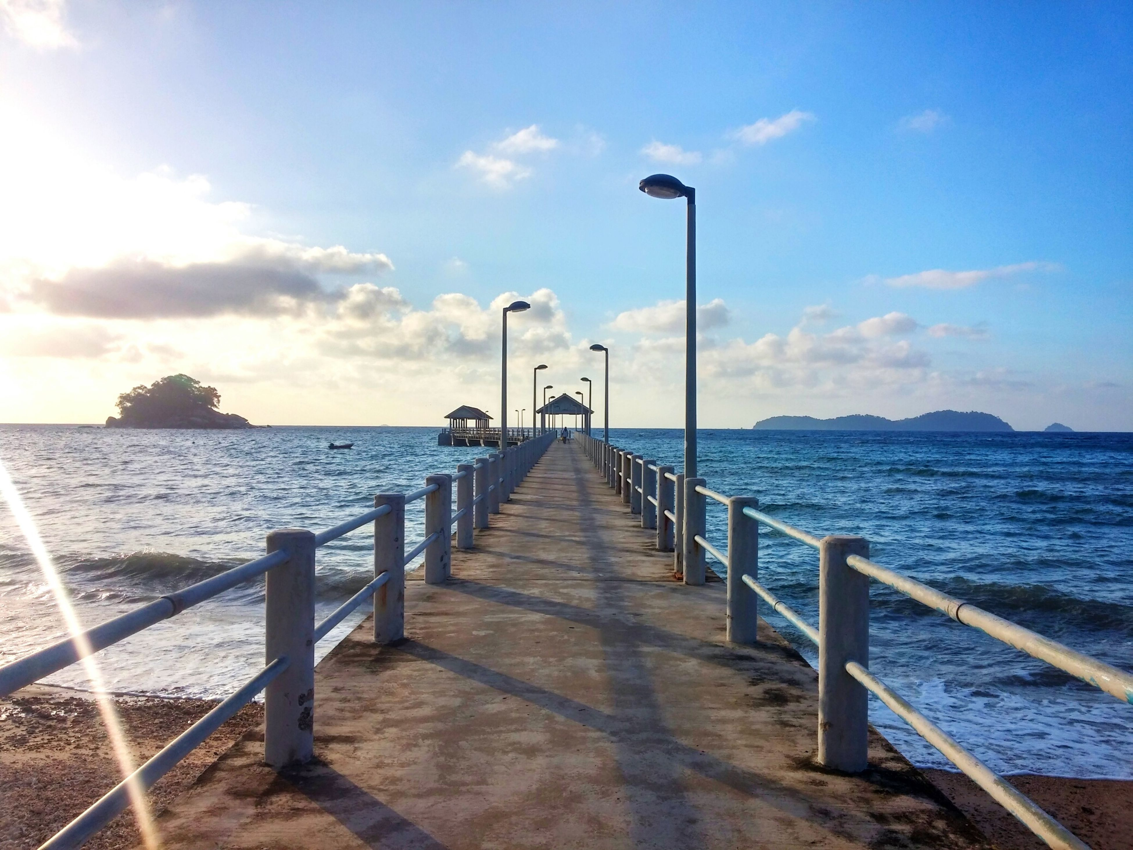 sea, water, the way forward, railing, sky, horizon over water, pier, tranquil scene, tranquility, scenics, street light, beauty in nature, diminishing perspective, nature, blue, jetty, idyllic, cloud - sky, vanishing point, long