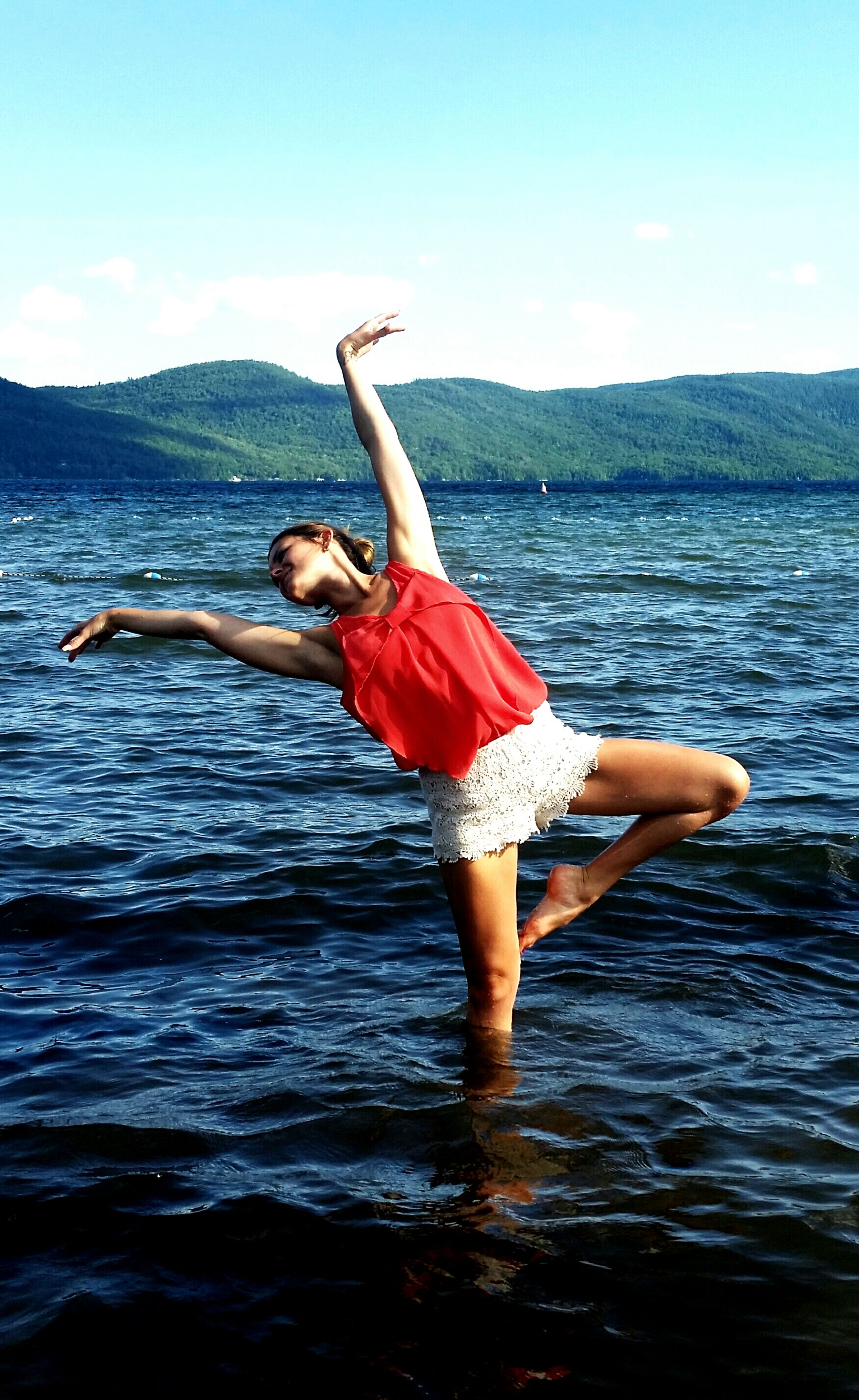 full length, water, arms outstretched, jumping, leisure activity, lifestyles, arms raised, mid-air, enjoyment, sea, young adult, freedom, carefree, fun, casual clothing, person, sky, standing