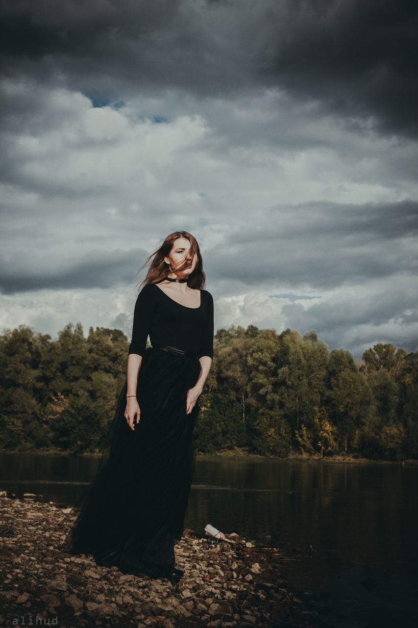 cloud - sky, sky, standing, full length, tree, black color, nature, lake, one person, outdoors, real people, young women, day, young adult, water, lifestyles, beautiful woman, beauty in nature, women, people