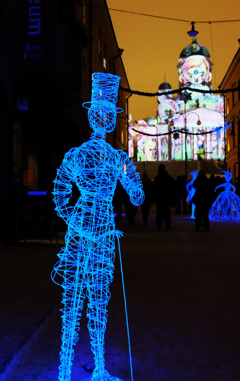 illuminated, real people, lighting equipment, night, blue, one person, celebration, built structure, architecture, full length, men, christmas decoration, indoors, people