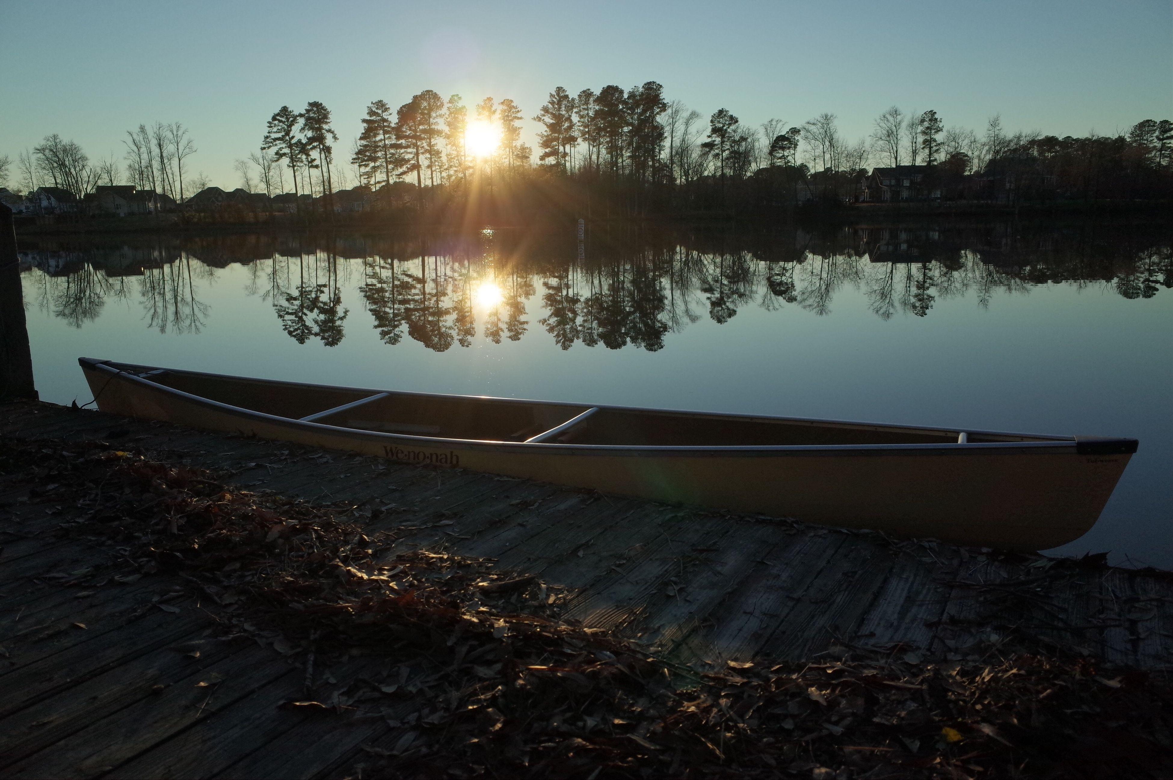 sun, water, sunset, sunlight, reflection, sky, lake, tranquility, tranquil scene, nautical vessel, boat, moored, nature, scenics, sunbeam, beach, tree, beauty in nature, transportation, sea