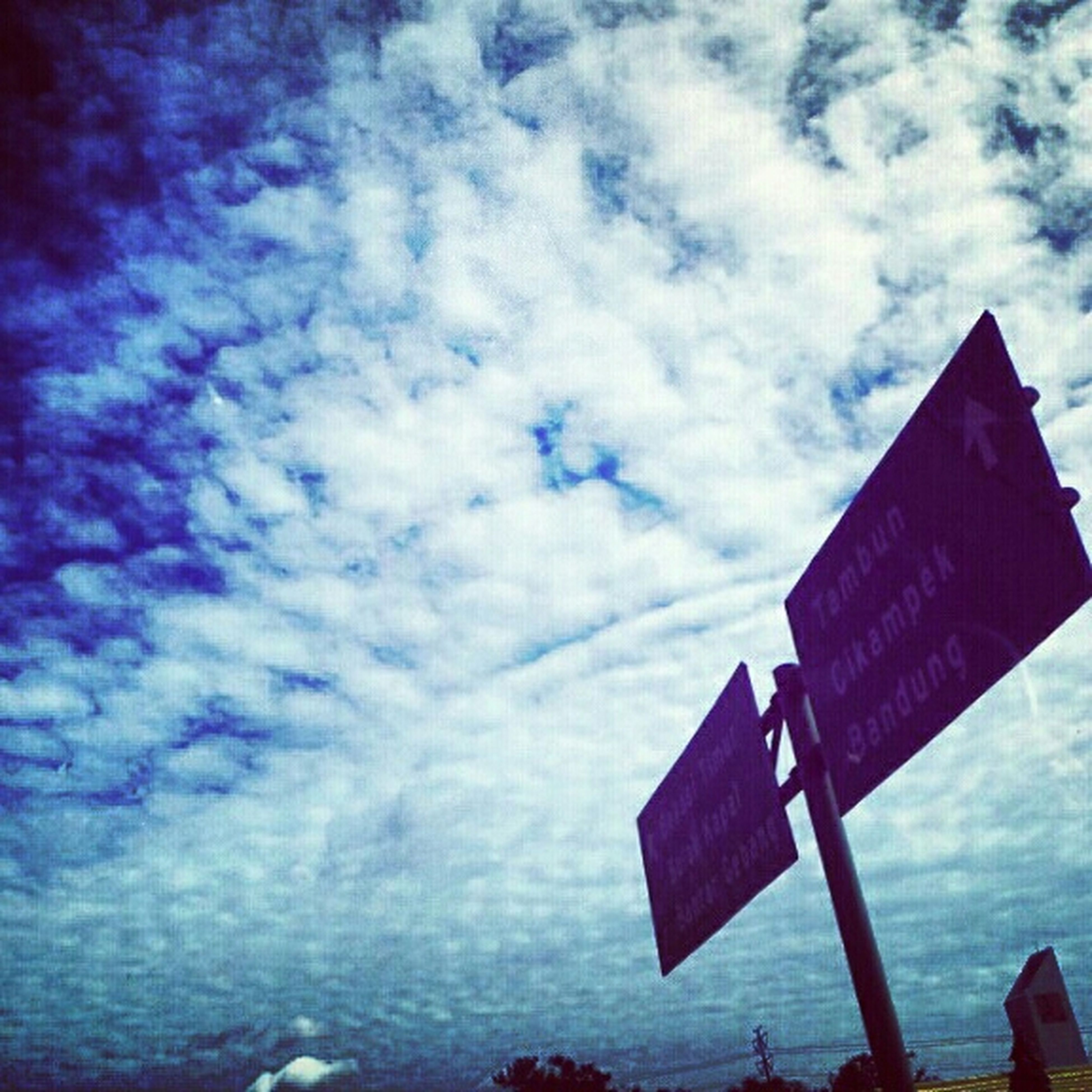 sky, guidance, text, communication, cloud - sky, western script, sign, information sign, cloud, cloudy, direction, low angle view, road sign, directional sign, blue, information, no people, weather, nature, day