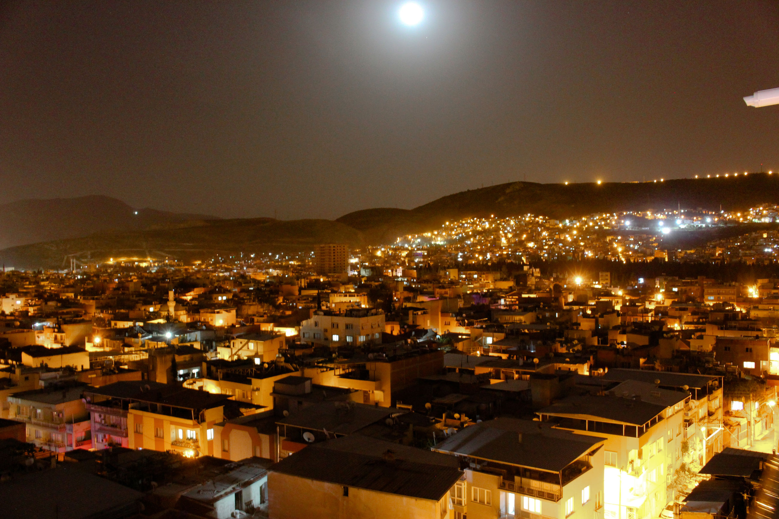 illuminated, architecture, night, building exterior, crowded, built structure, mountain, outdoors, city, moon, cityscape, town, house, sky, residential building, roof