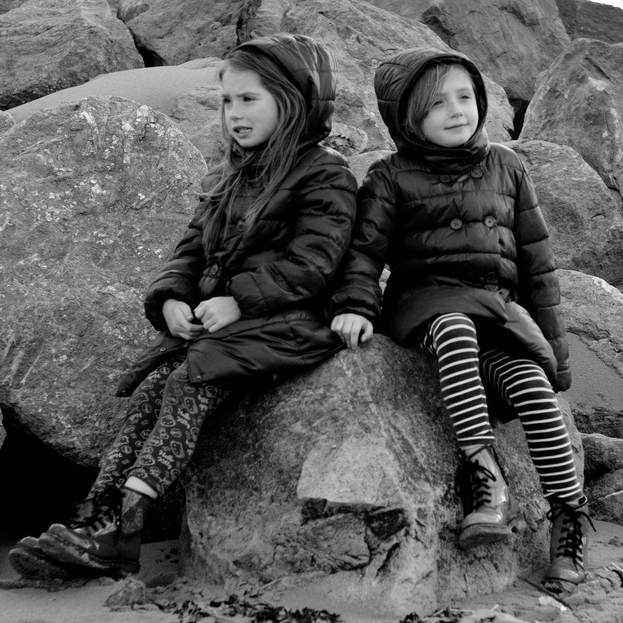 Girls Sitting On Rock At Beach