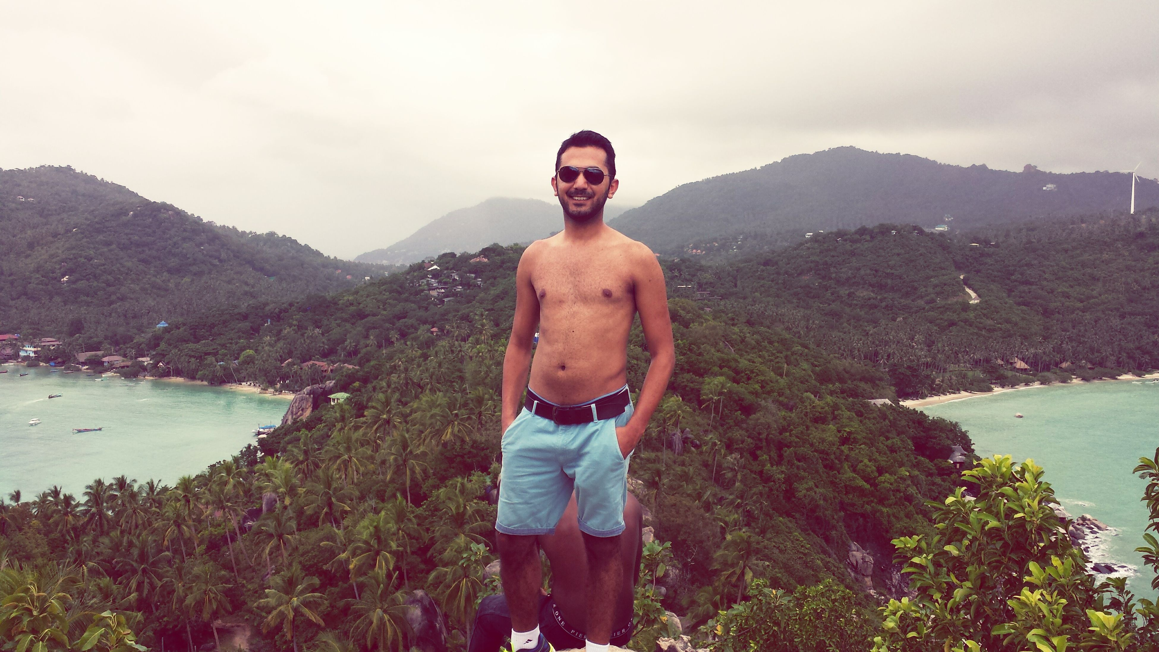 mountain, young adult, person, lifestyles, young men, looking at camera, casual clothing, leisure activity, portrait, water, smiling, standing, sky, mountain range, front view, three quarter length, sunglasses, scenics