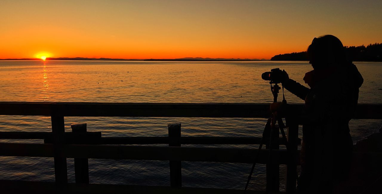 Sunset Photography Themes Camera - Photographic Equipment Water Sea Railing Digital Camera Technology Leisure Activity One Person Outdoors Photographer Scenics Nature Beauty In Nature People Adult Adults Only Day Sky Tranquility Architecture Built Structure Dusk Travel Destinations
