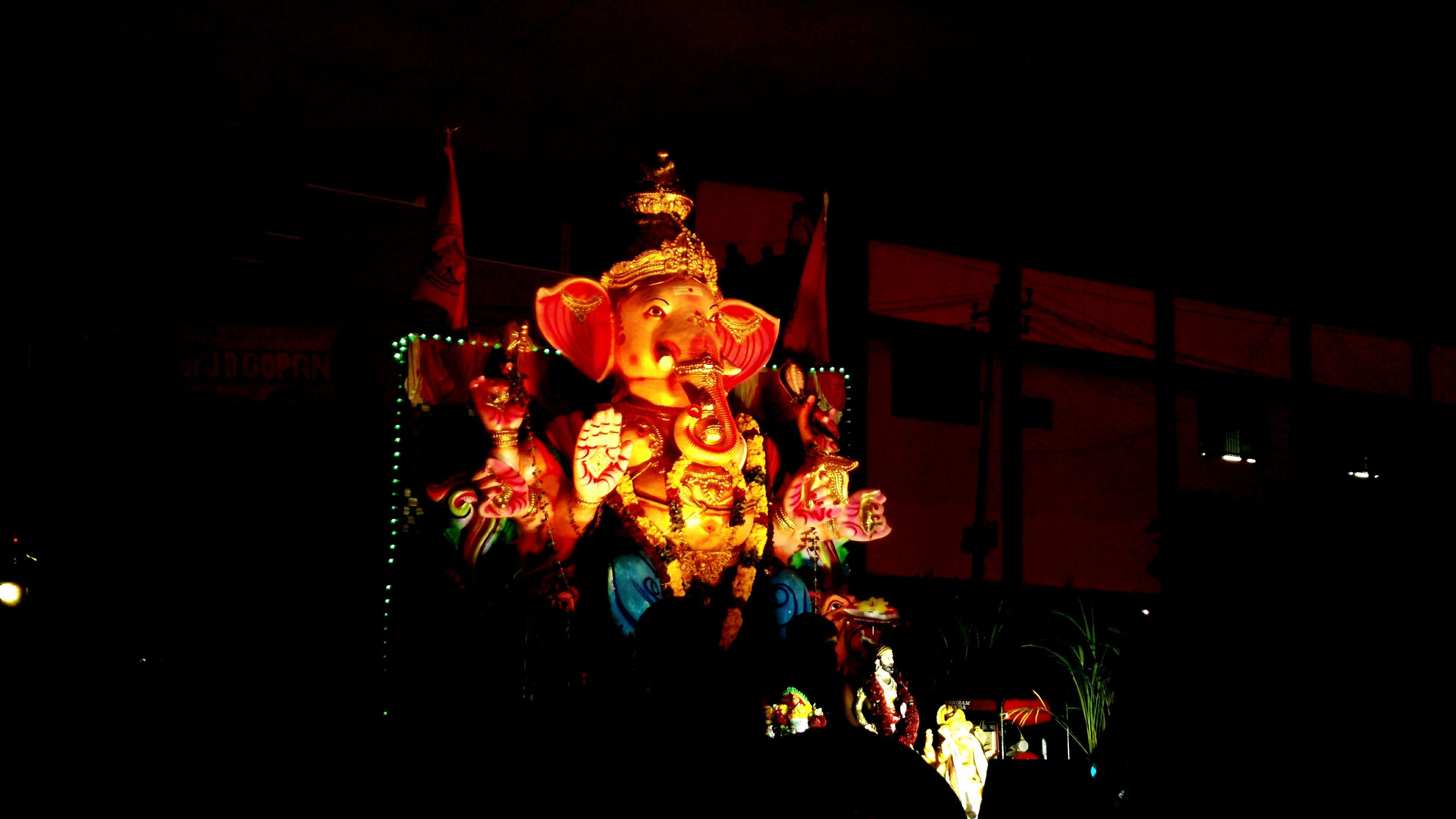 human representation, low angle view, illuminated, tradition, religion, celebration, spirituality, lantern, cultures, night, place of worship, decoration, culture, creativity, orange color