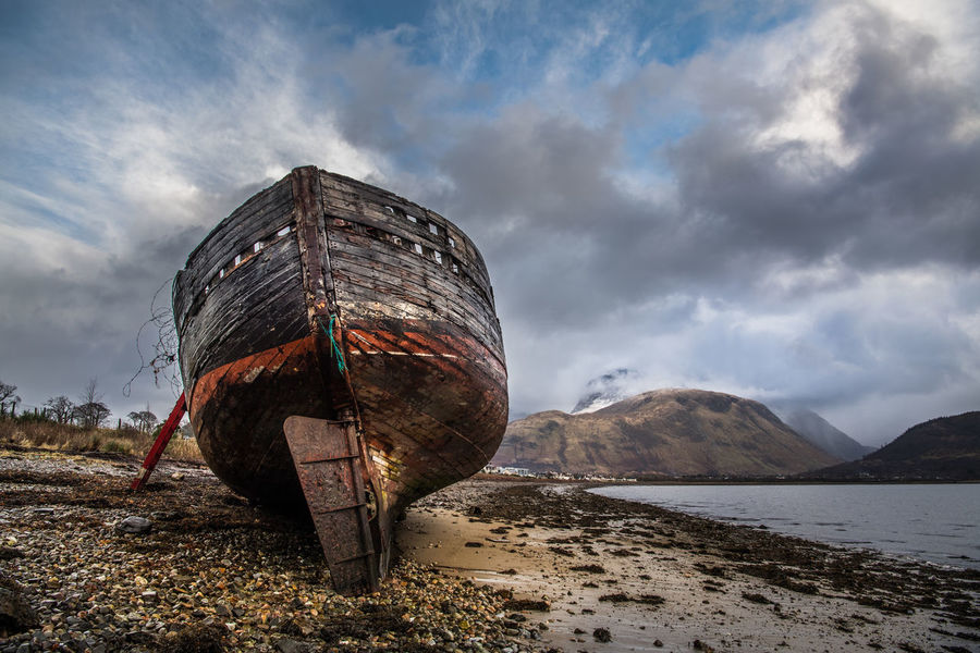 Wreck of old fishing boat and view towards Fort William, Highland and the snow capped peak of Ben Nevis from the shore of Loch Linnhe at Corpach, Scottish Highlands. **The boat was originally named MV Dayspring, and built in 1975 as a fishing boat, bringing in mackerel and herring. New owners renamed the ship the Golden Harvest. **Her final voyage took place in 2001. The boat slipped its moorings at Kinlochleven Pier after a heavy storm and has lain in the same spot since the 8th December 2011. Photographed on the 8th December 2017. Scotland Abandoned Beach Boat Cloud - Sky Highlands Nature Nautical Vessel No People Outdoors Sea Water Wrecked Wrecked Boat.