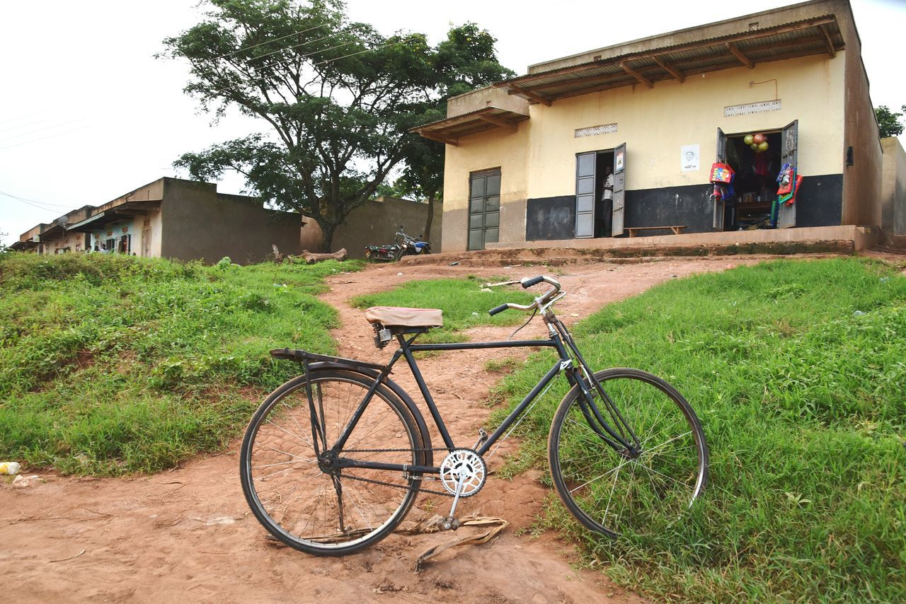 architecture, building exterior, built structure, bicycle, house, transportation, day, outdoors, land vehicle, mode of transport, no people, residential building, grass, tree, stationary, sky