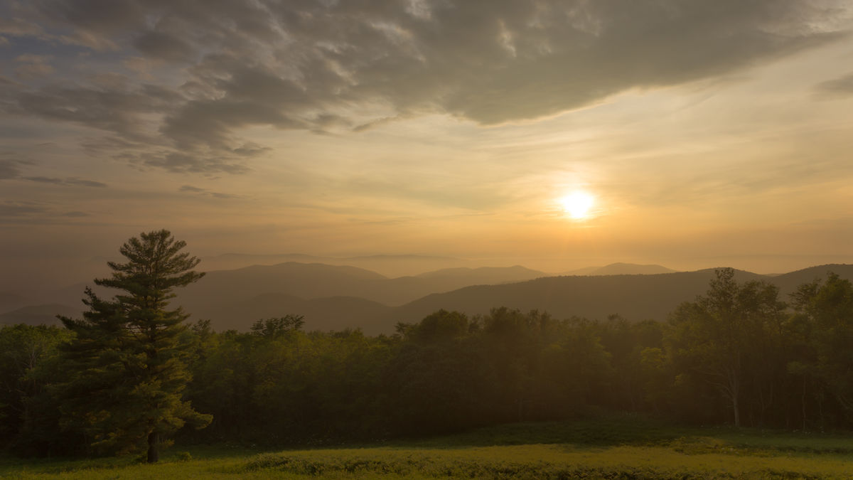 The sun sets over the Blue Ridge Mountains in Shenandoah National Park as fog lays low in the valleys and clouds create a warm glow in the sky Beauty In Nature Cloud Cloud - Sky Cloudy Idyllic Landscape Majestic Mountain Mountain Range Nature No People Non Urban Scene Non-urban Scene Orange Color Outdoors Remote Scenics Shenandoah National Park Sky Sun Sunset Tranquil Scene Tranquility Travel Destinations Tree