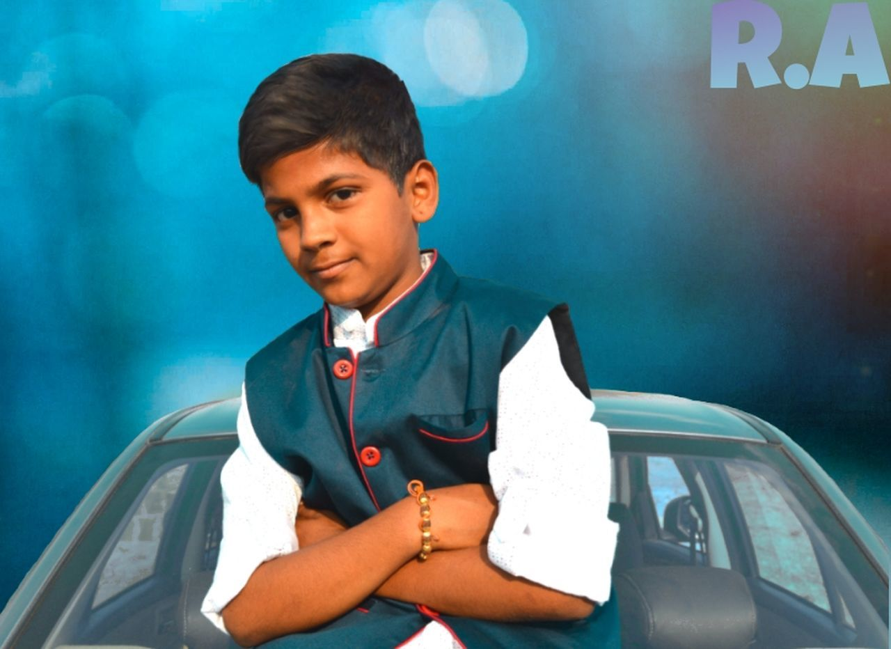 one person, looking at camera, boys, portrait, car, education, childhood, transportation, front view, real people, sitting, lifestyles, standing, school uniform, indoors, day, people