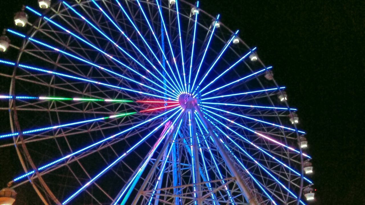 Low Angle View Of Illuminated Ferris Wheel At Sky Fun