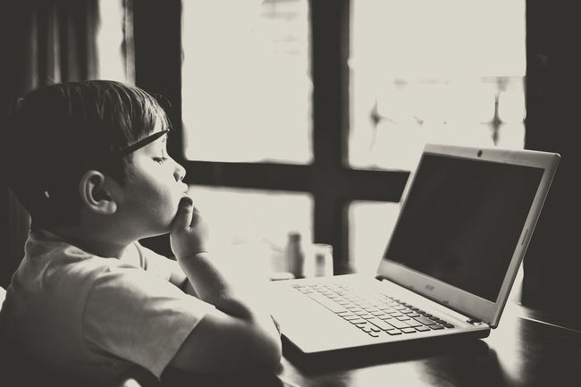 Young student sitting in front of a laptop, thinking Black And White Laptop Student Toddler  Young Boy Learning Homework Back To School Studying Thinker Thoughts Writting Inspirational Inspirations Inspired Think Thinking Black Screen Thoughtful