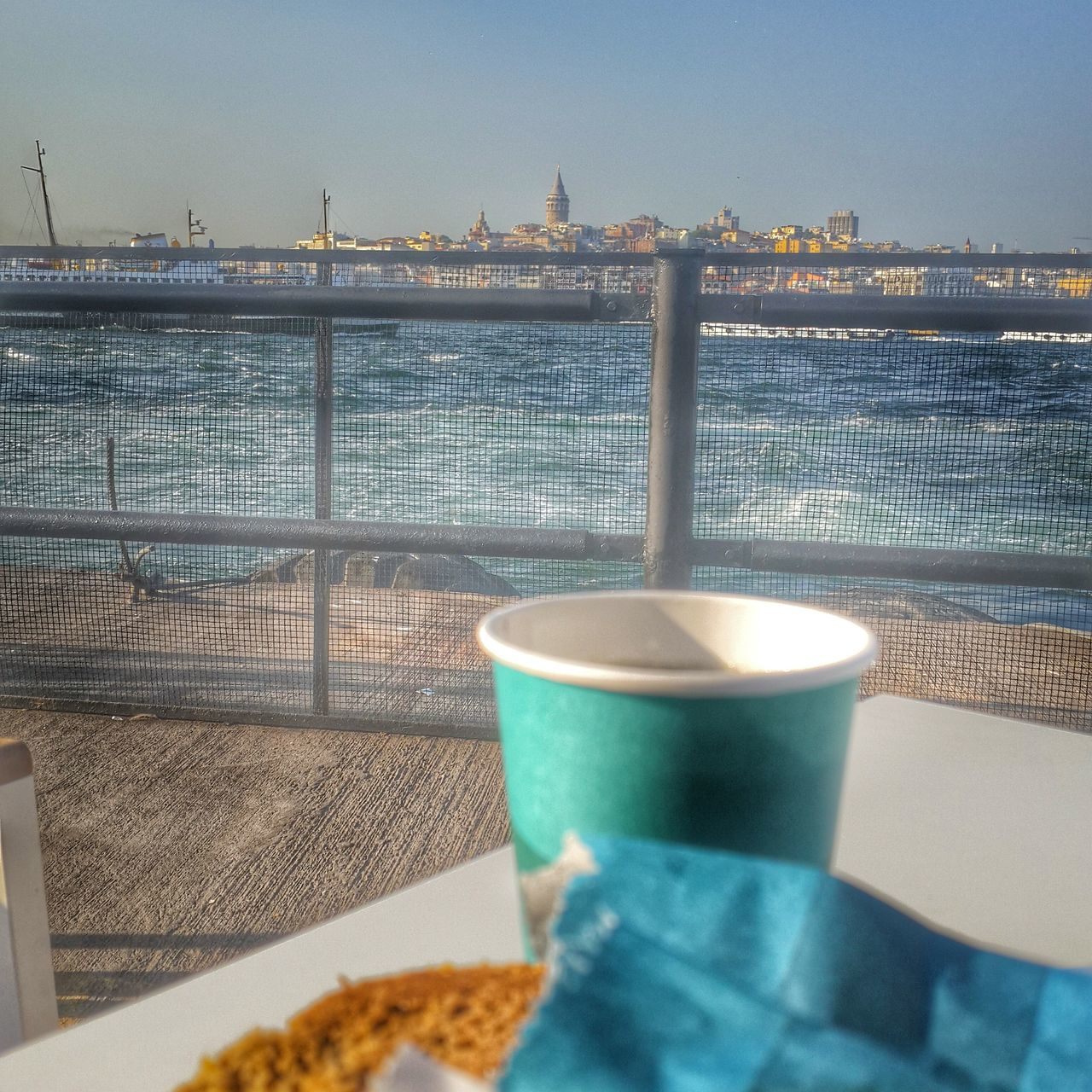 water, food and drink, railing, coffee cup, refreshment, drink, no people, table, sea, food, day, clear sky, built structure, indoors, freshness, close-up, architecture, sky, ready-to-eat