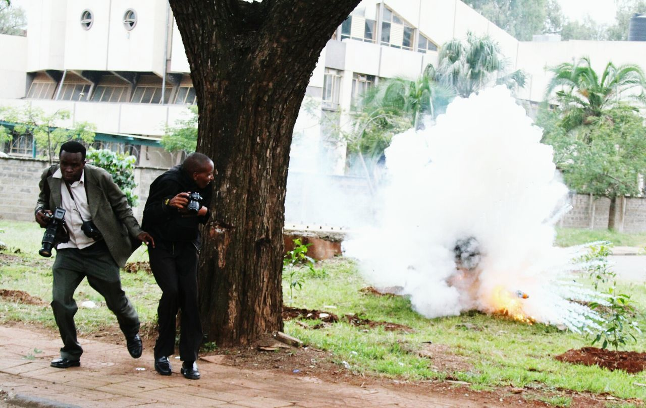 Journalists try to take cover after a teargas explodes near them during a demonstration by university student in Nairobi. Journalism Journalist Photography Journalist Finger Occupational Hazard Teargas Taking Cover. Journalists