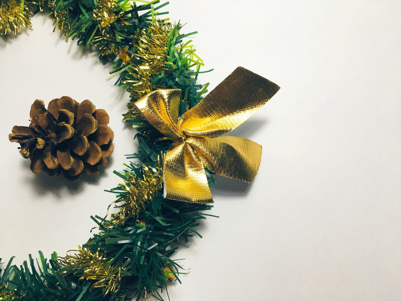 Close-Up Of Christmas Wreath And Pine Cone On Table