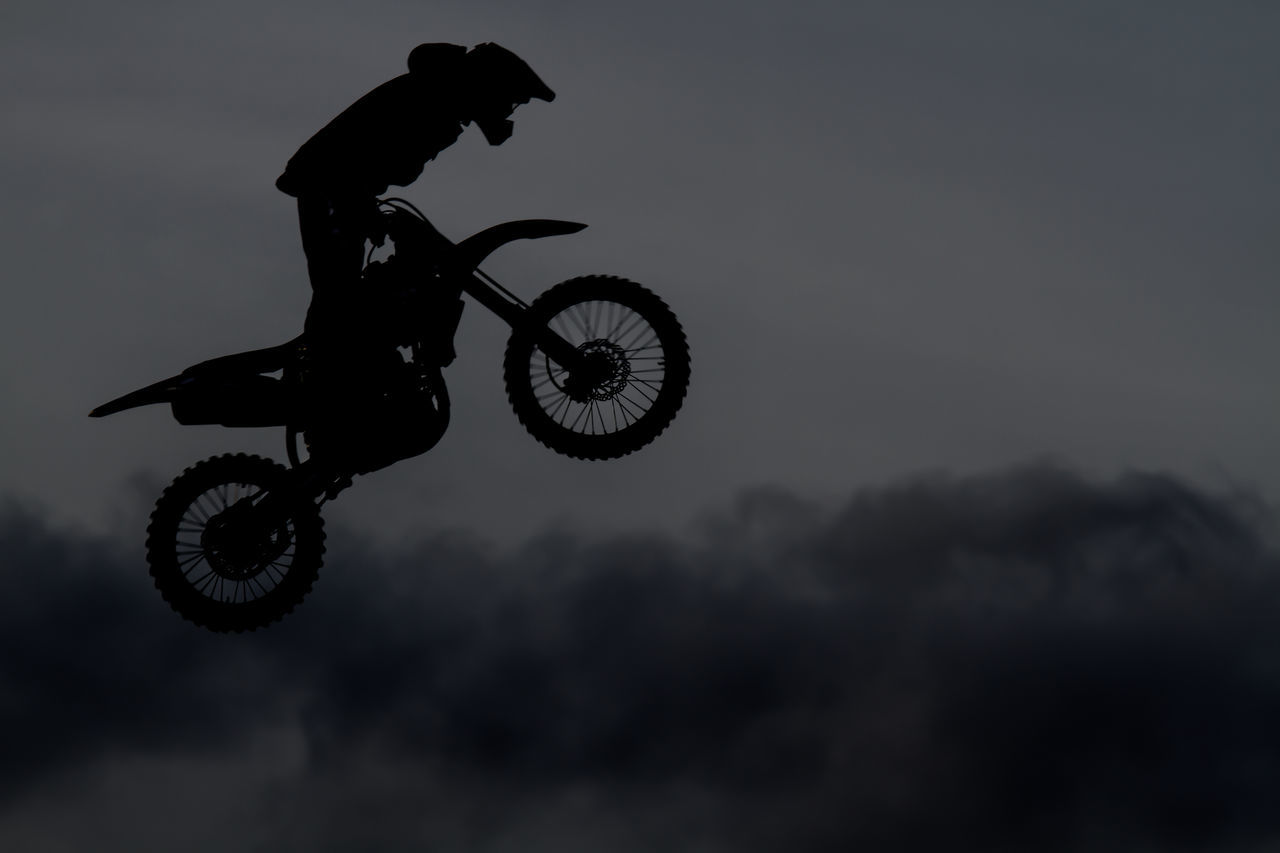 Side View Of Motocross Racer Performing Mid-Air Stunt