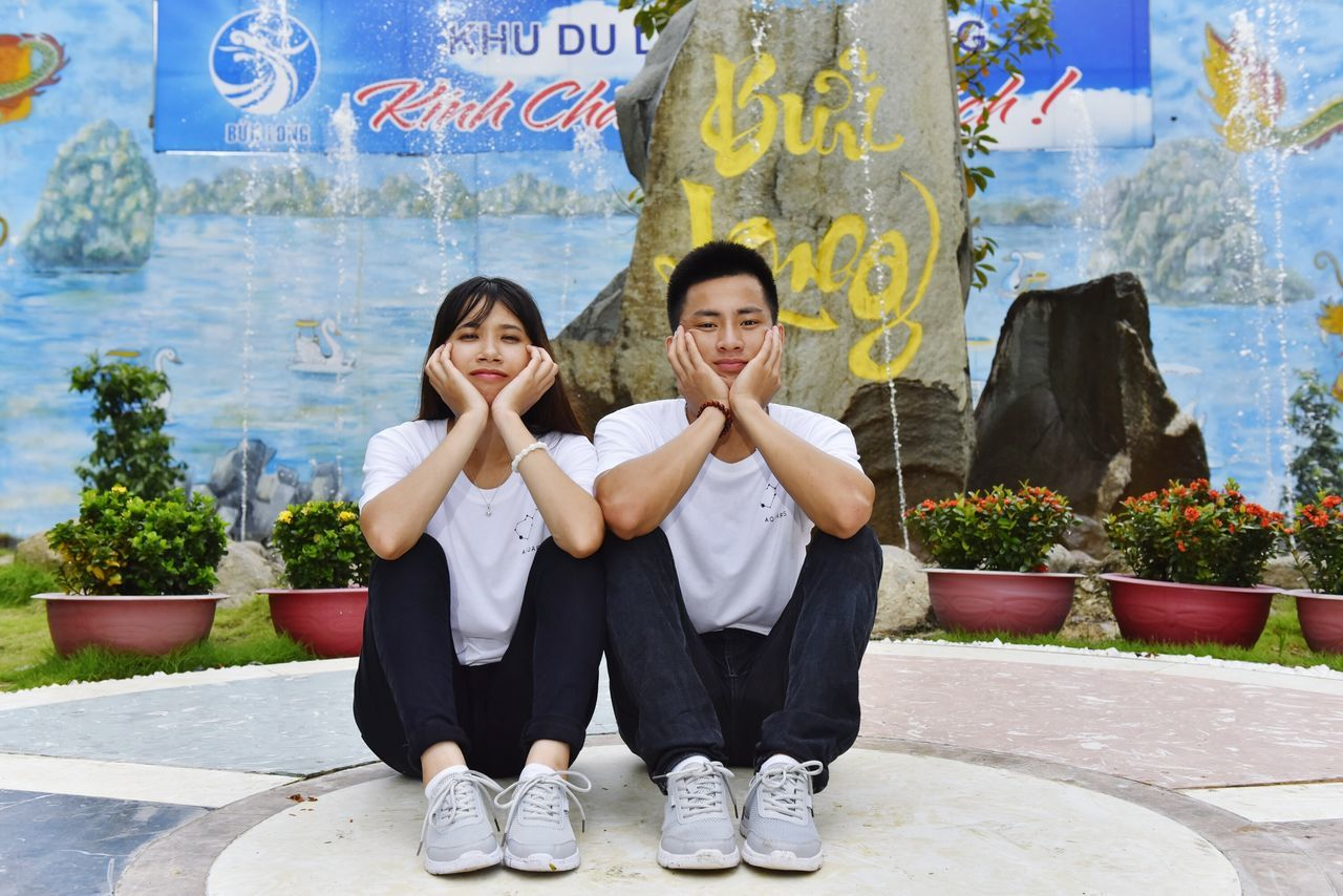 two people, looking at camera, full length, togetherness, smiling, portrait, day, front view, outdoors, happiness, young adult, sitting, young women, friendship, people, adult, adults only