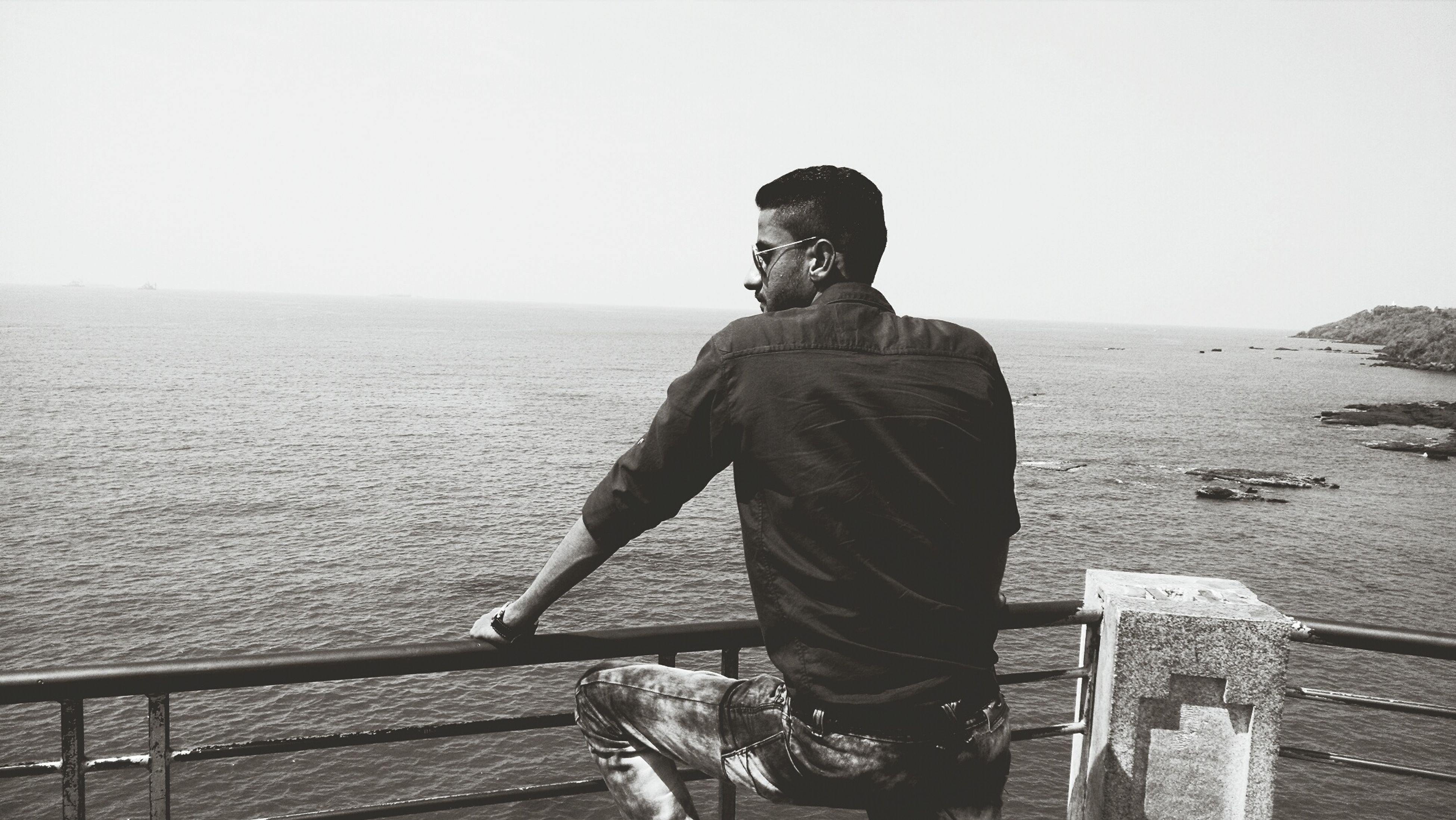 sea, water, rear view, clear sky, horizon over water, lifestyles, standing, copy space, leisure activity, casual clothing, full length, sky, three quarter length, men, looking at view, tranquil scene, tranquility, nature