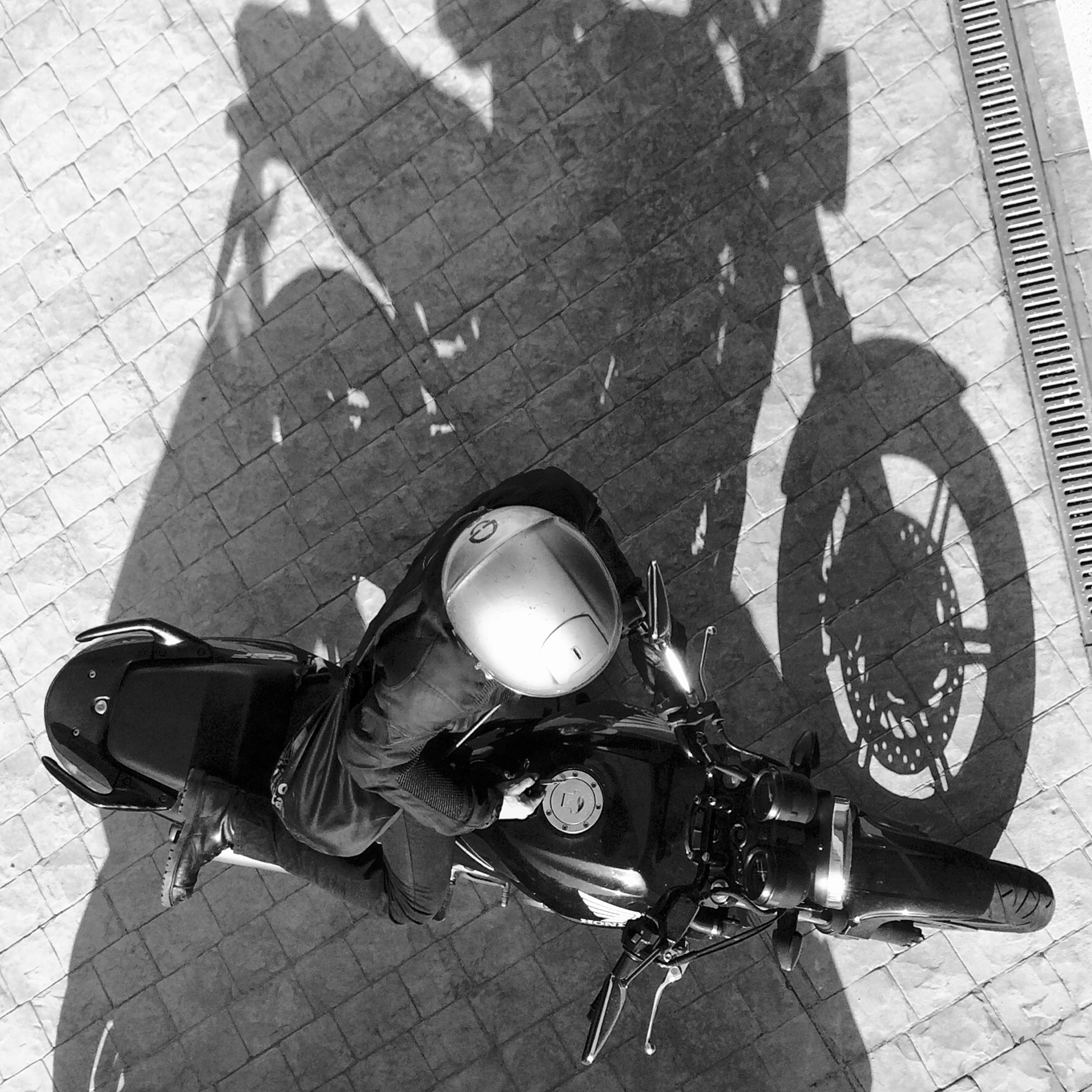 street, lifestyles, bicycle, men, high angle view, leisure activity, outdoors, land vehicle, day, transportation, shadow, holding, standing, sidewalk, sunlight, casual clothing, road, shoe