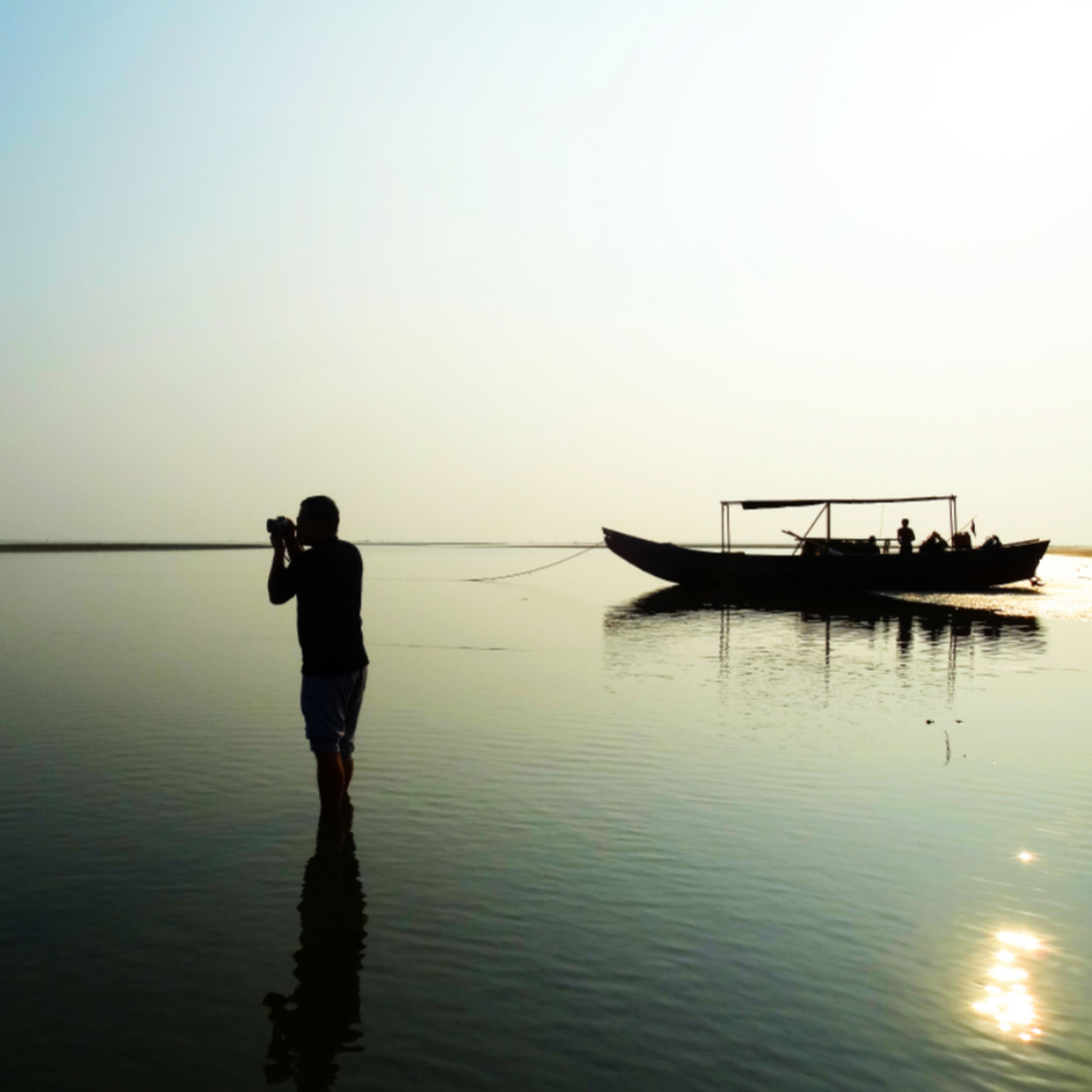 water, clear sky, silhouette, sunset, nautical vessel, sea, reflection, copy space, tranquility, tranquil scene, boat, transportation, waterfront, scenics, beauty in nature, nature, horizon over water, men, mode of transport