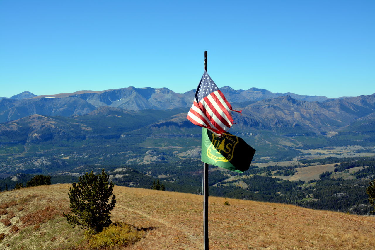 flag, patriotism, mountain, blue, beauty in nature, day, flag pole, tranquil scene, clear sky, nature, mountain range, no people, tranquility, outdoors, scenics, landscape, stars and stripes, sky