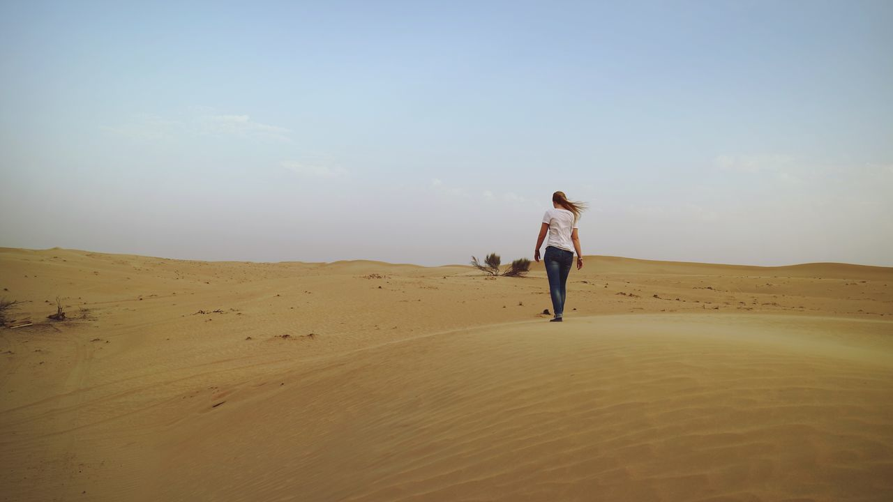 sand, desert, sky, full length, landscape, nature, one person, real people, walking, sand dune, leisure activity, outdoors, beach, day, lifestyles, arid climate, standing, women, energetic, beauty in nature, young adult, people