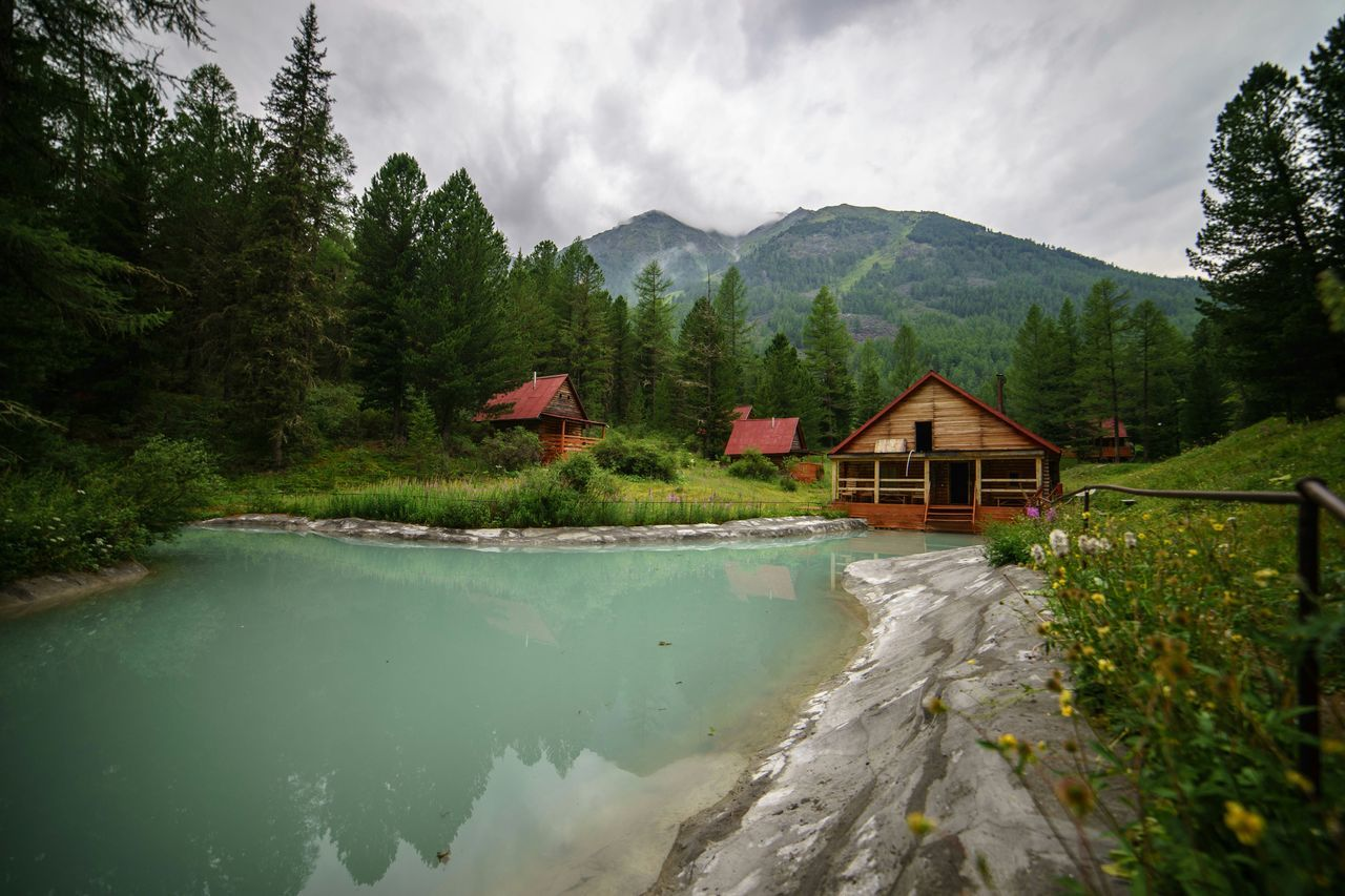 Cottages On Field By Pond Against Mountains