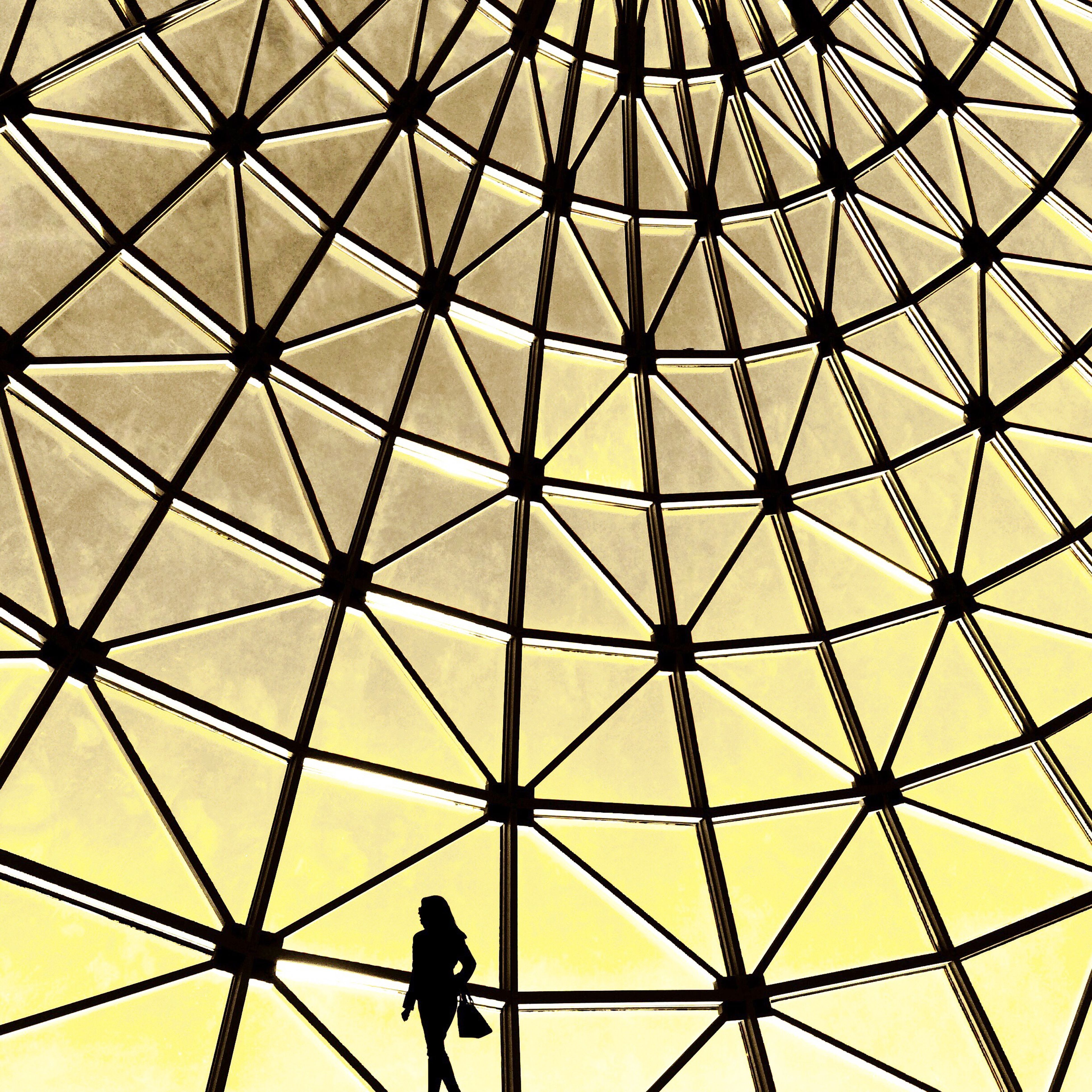 indoors, ceiling, architecture, built structure, pattern, low angle view, men, full frame, lifestyles, backgrounds, glass - material, leisure activity, modern, architectural feature, standing, geometric shape, silhouette, design