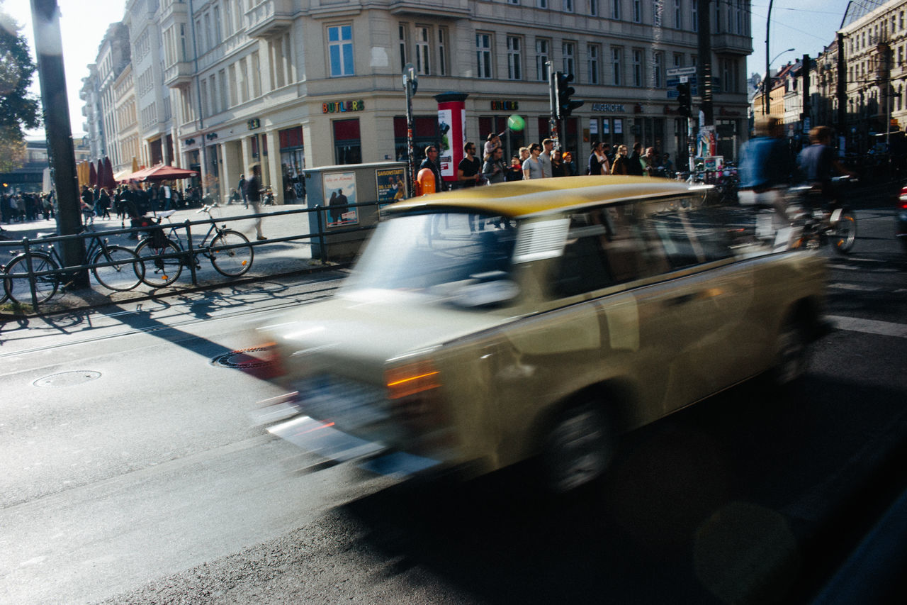blurred motion, architecture, large group of people, building exterior, built structure, transportation, motion, real people, mode of transport, city, land vehicle, city life, men, day, outdoors, women, people, adult