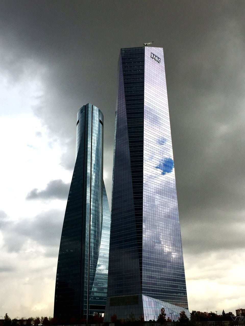 architecture, low angle view, built structure, sky, modern, skyscraper, tall - high, cloud - sky, building exterior, no people, travel destinations, day, outdoors, city