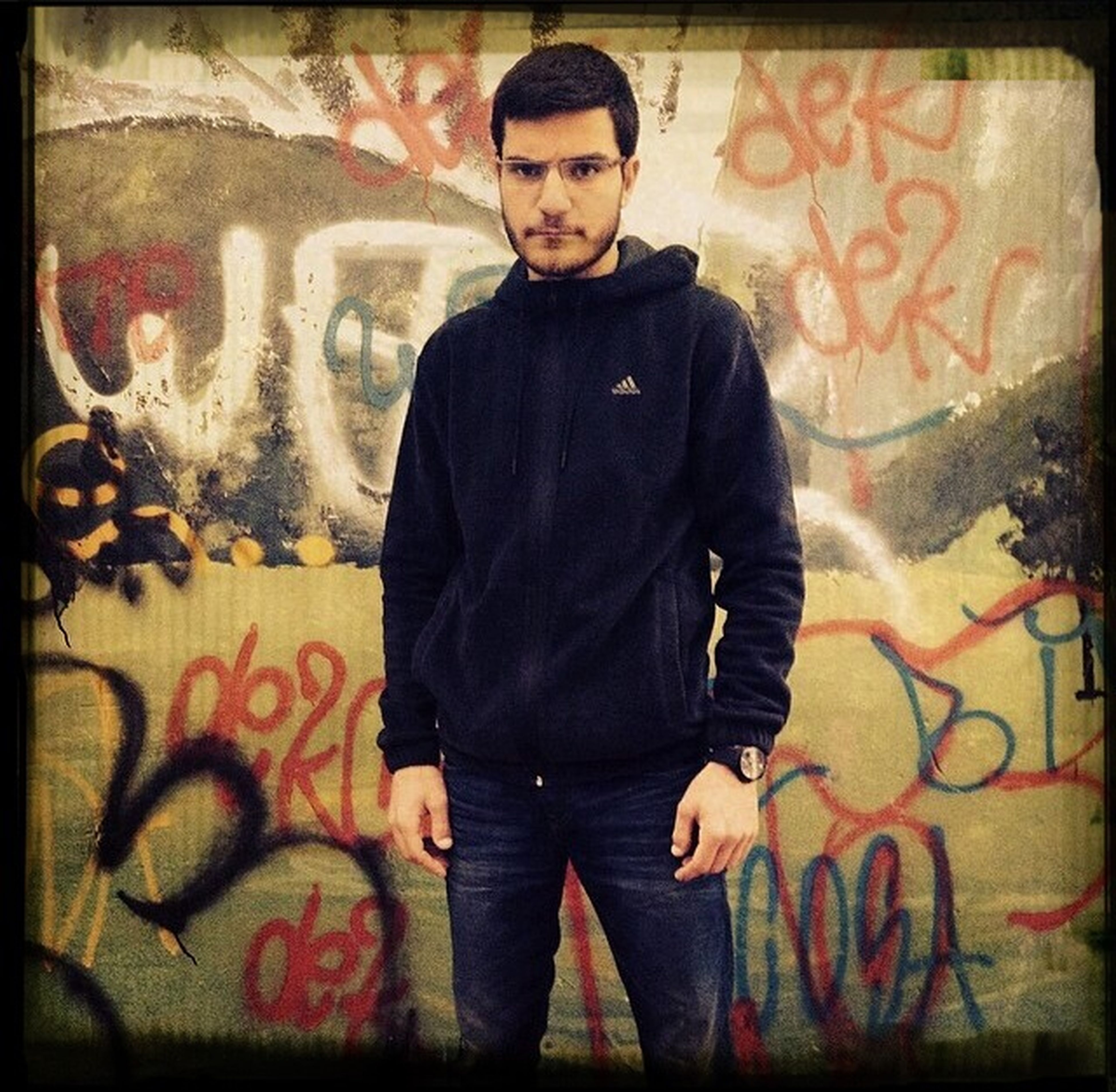young adult, lifestyles, transfer print, indoors, graffiti, casual clothing, portrait, looking at camera, front view, person, auto post production filter, young men, leisure activity, three quarter length, standing, wall - building feature, text