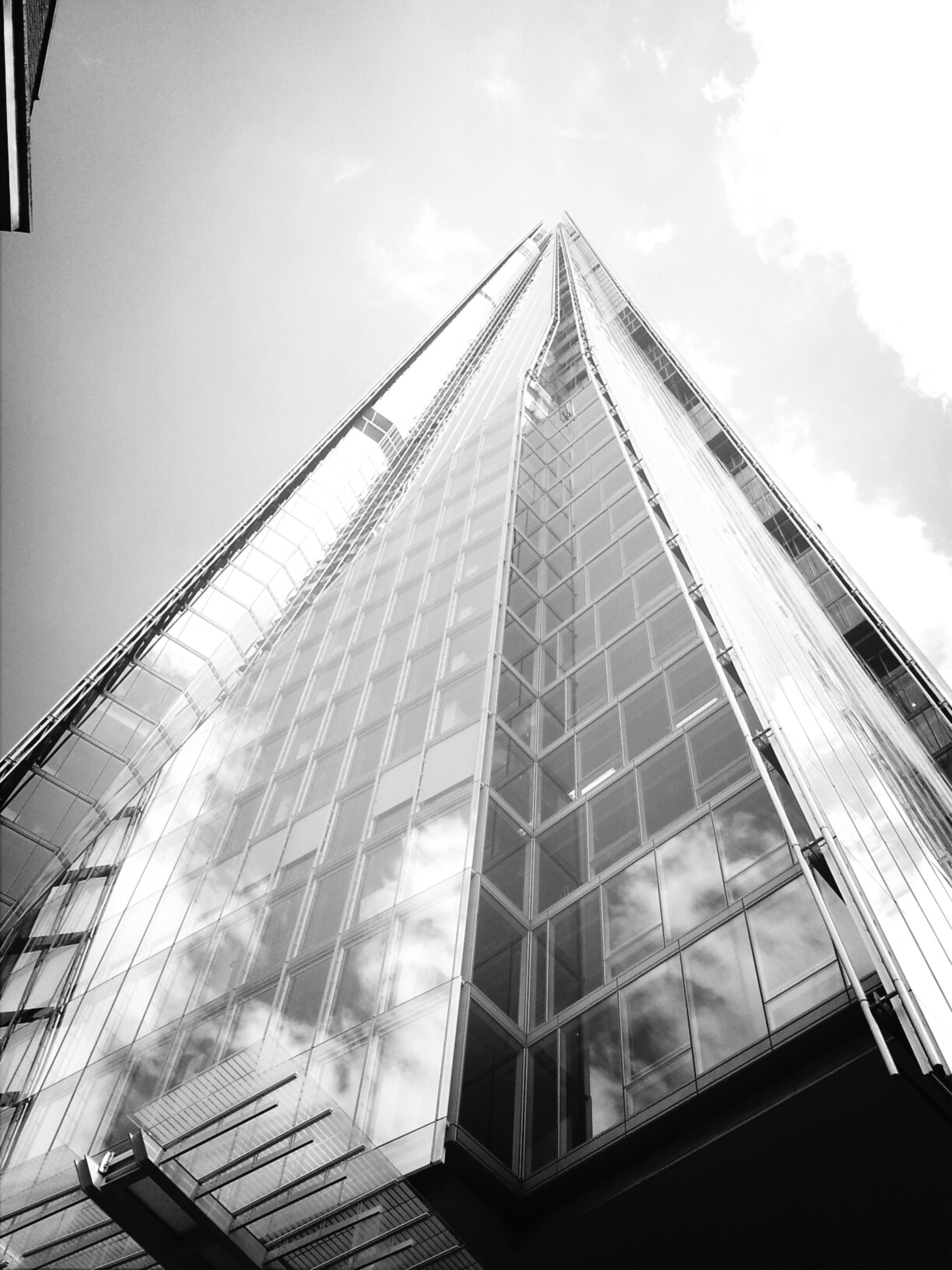 architecture, built structure, building exterior, low angle view, sky, glass - material, modern, city, skyscraper, office building, building, tall - high, reflection, day, cloud - sky, no people, outdoors, window, cloud, development