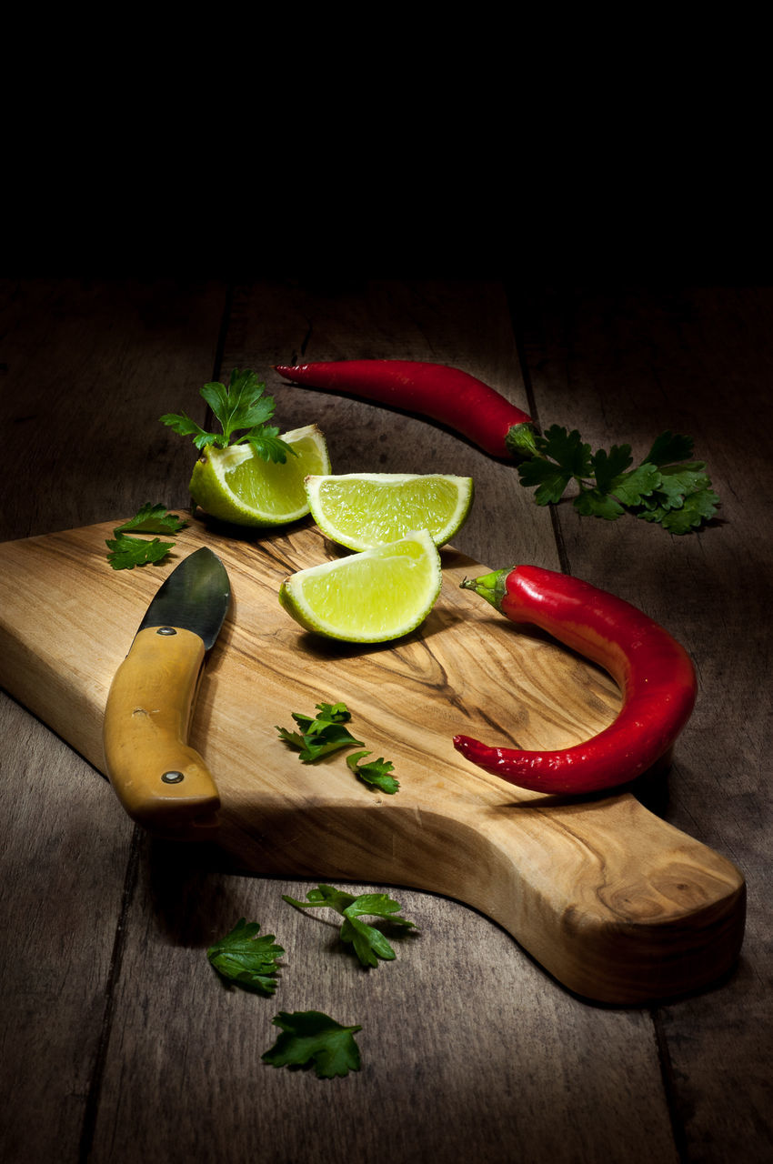 High Angle View Of Lime With Red Chili Pepper On Cutting Board