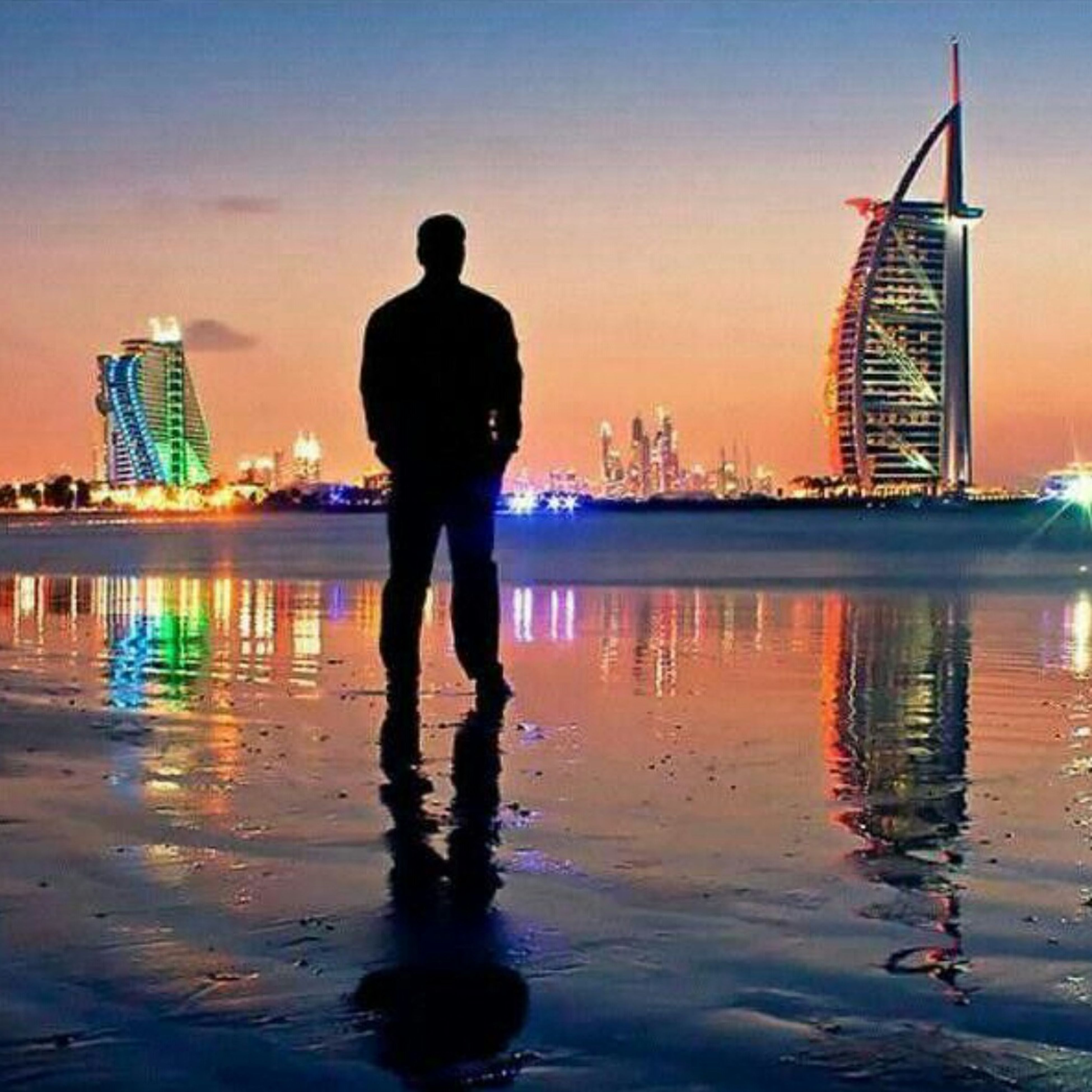 water, sunset, reflection, lifestyles, sky, leisure activity, full length, sea, rear view, built structure, silhouette, standing, architecture, building exterior, men, waterfront, pier, outdoors