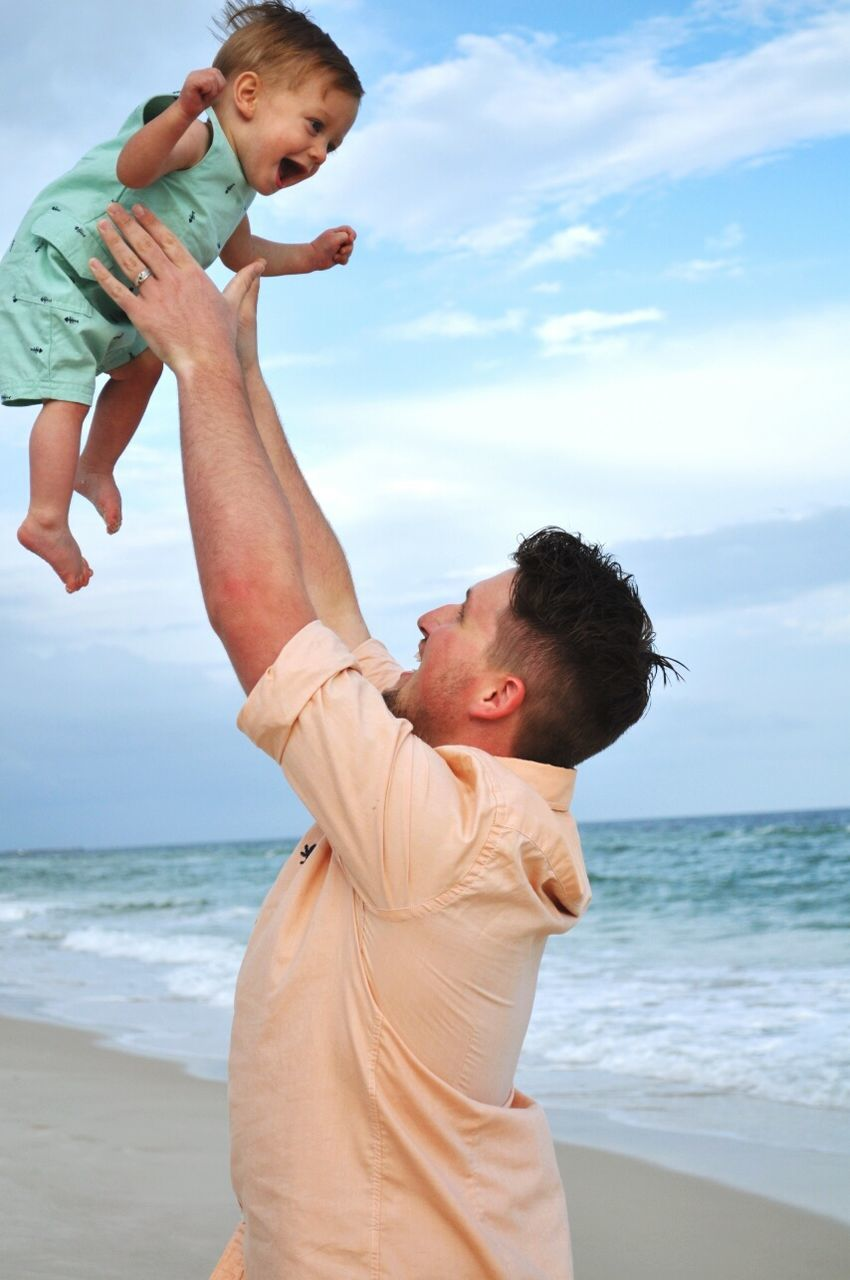Father Playing With Son At Beach