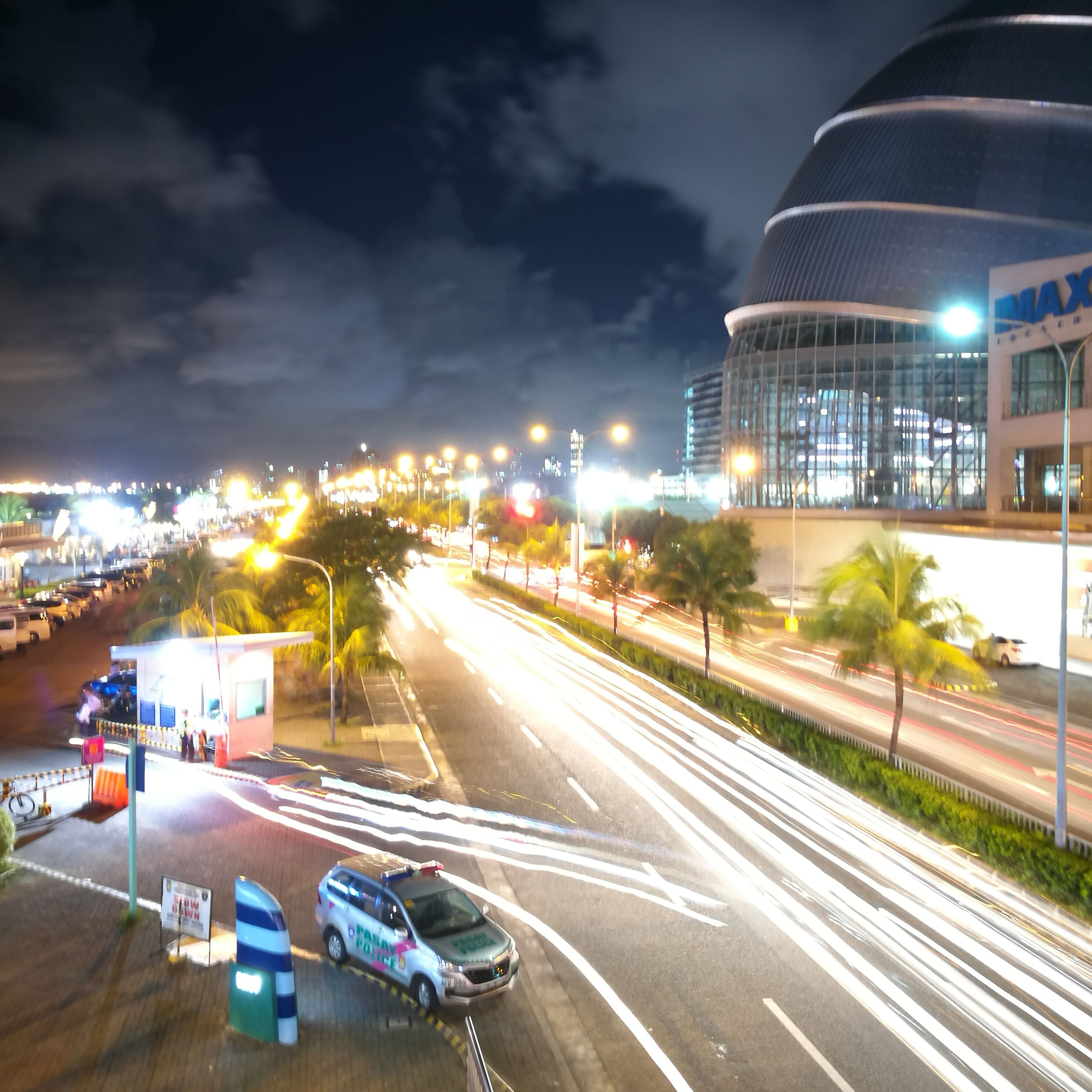illuminated, night, road, city, architecture, street, building exterior, light trail, built structure, long exposure, transportation, high angle view, motion, outdoors, city life, car, no people, high street, sky, tree, cityscape