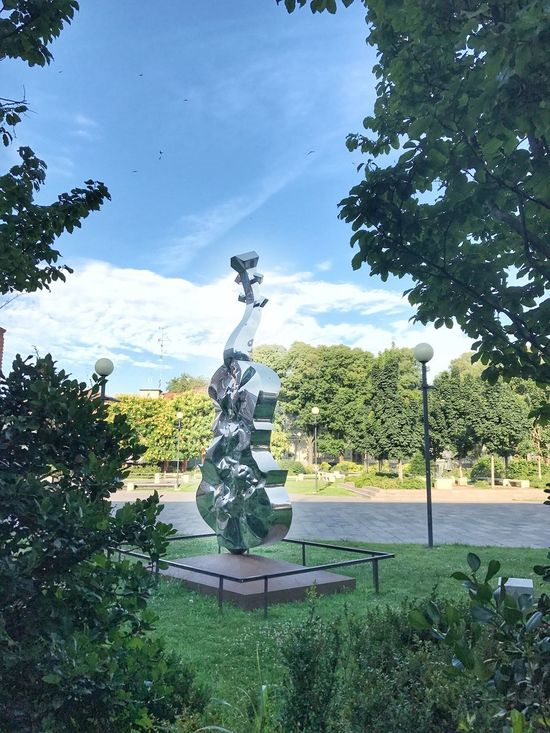 Violin Museum Sculpture by Helidon Xchixcha Tree Human Representation Statue Sculpture Male Likeness Art And Craft Growth Day Green Color Sky No People Cloud - Sky Nature Outdoors Plant Beauty In Nature Music Musical Instrument Violin