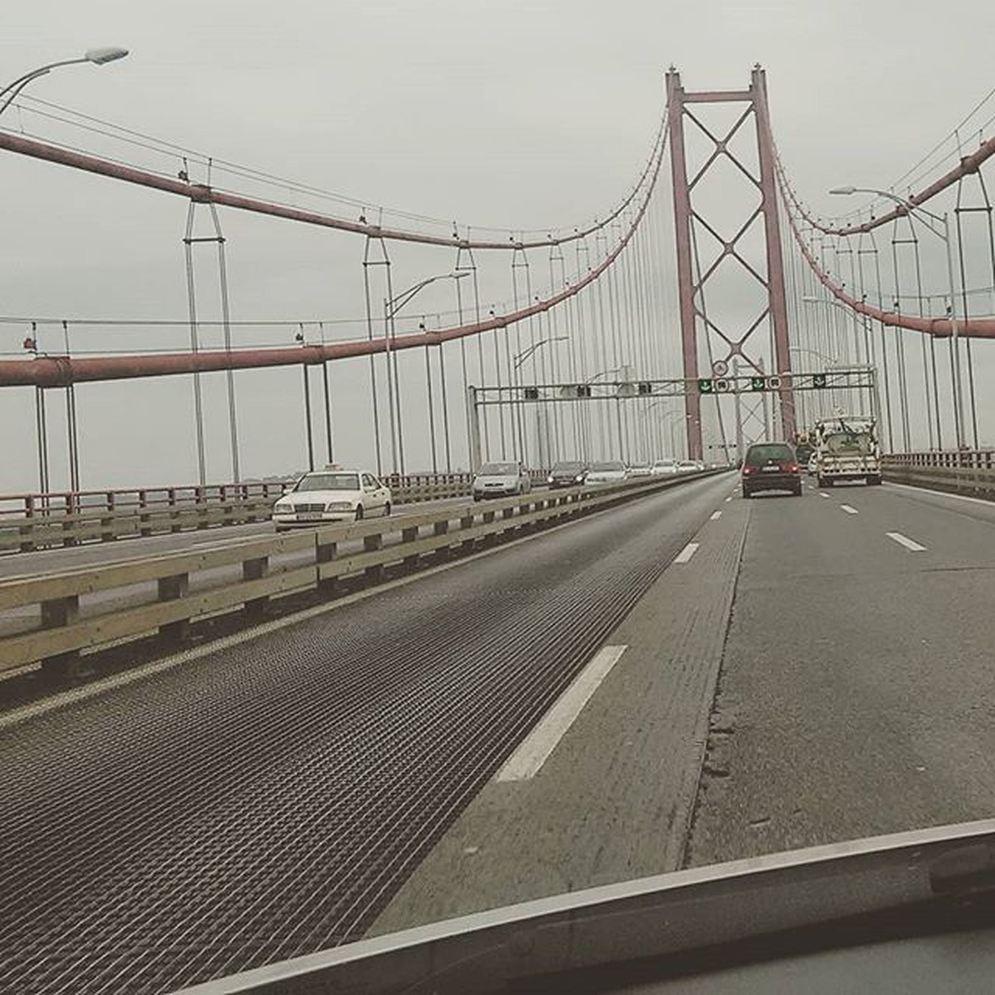 built structure, architecture, connection, transportation, bridge - man made structure, engineering, clear sky, sky, building exterior, metal, diminishing perspective, bridge, railing, city, outdoors, the way forward, day, no people, suspension bridge, road