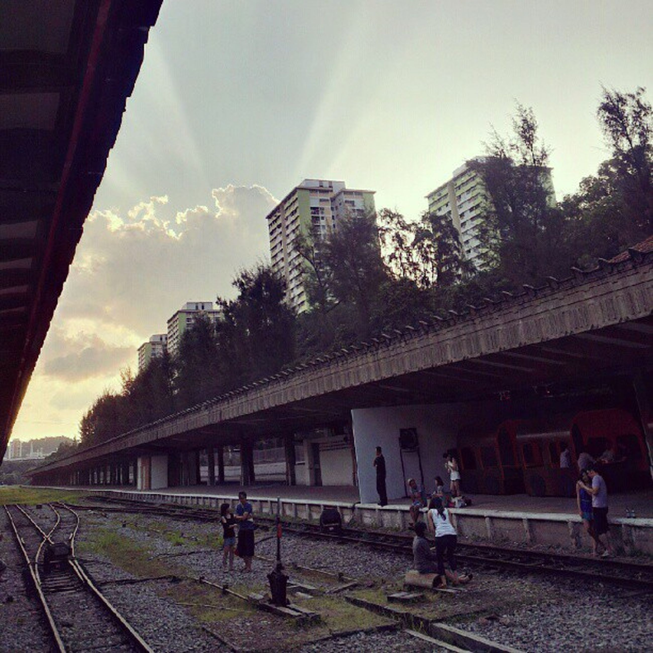 architecture, built structure, building exterior, lifestyles, men, person, sky, city, leisure activity, walking, large group of people, city life, tree, sunlight, railroad track, railing, full length, day, cloud - sky
