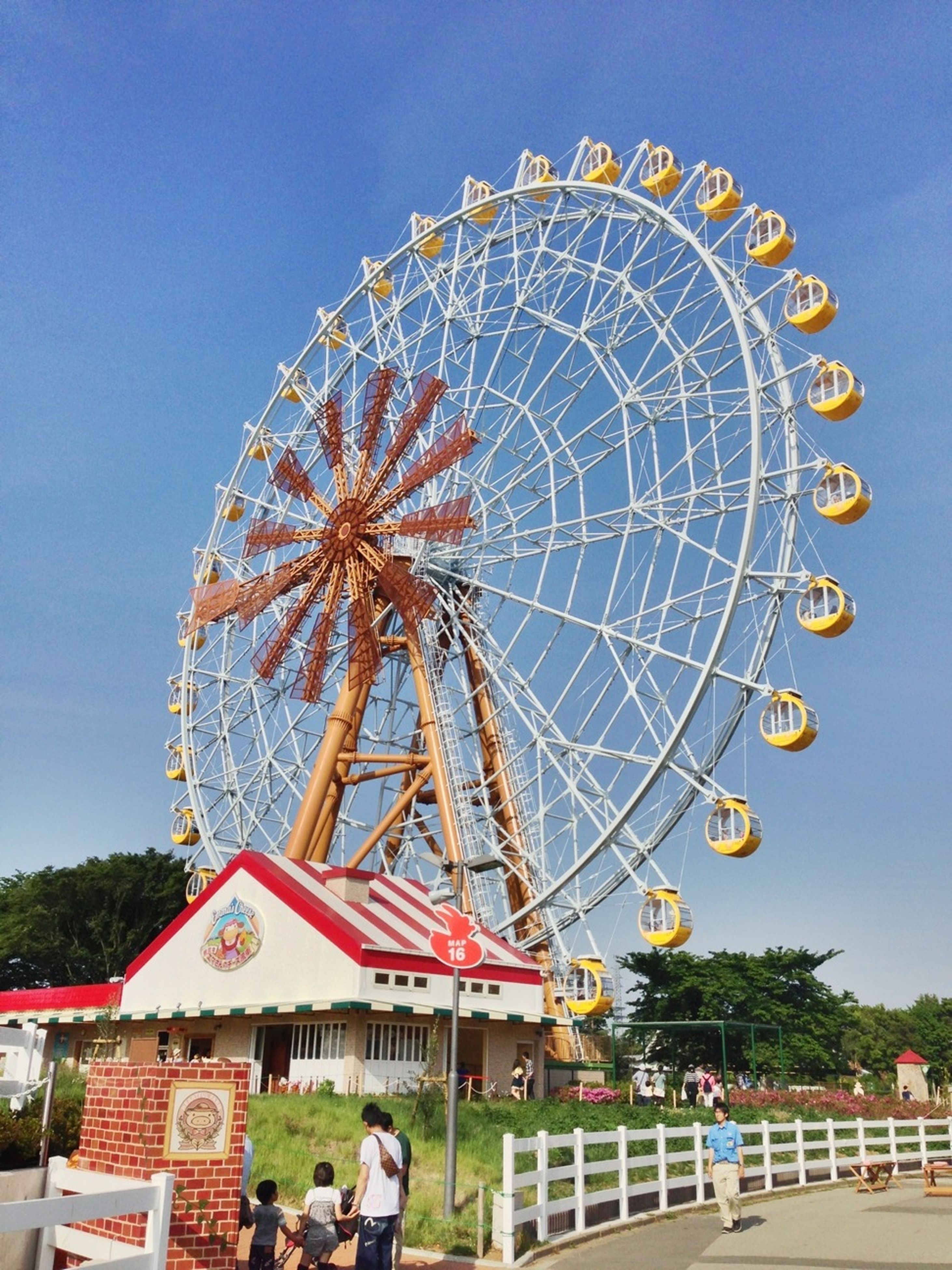 amusement park, amusement park ride, ferris wheel, arts culture and entertainment, low angle view, leisure activity, clear sky, fun, enjoyment, tree, sky, built structure, architecture, incidental people, outdoors, traveling carnival, blue, large, big wheel, day