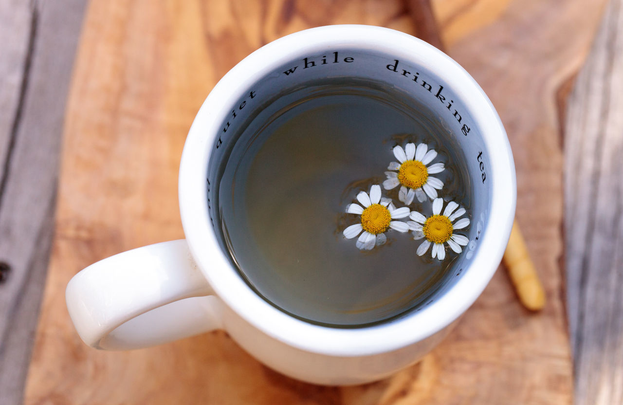 Chamomile tea with chamomile daisy flowers in a hot white cup on a wooden rustic cutting board and a spoon. This home remedy is known to help sleep and aid a sore throat Calm Chamomile Close-up Cup Of Tea Cutting Board Daisy Day Flower Herb Herbal Herbal Tea Mug No People Relaxing Relaxing Moments Sleep Tea Tea Time Tranquility Wood