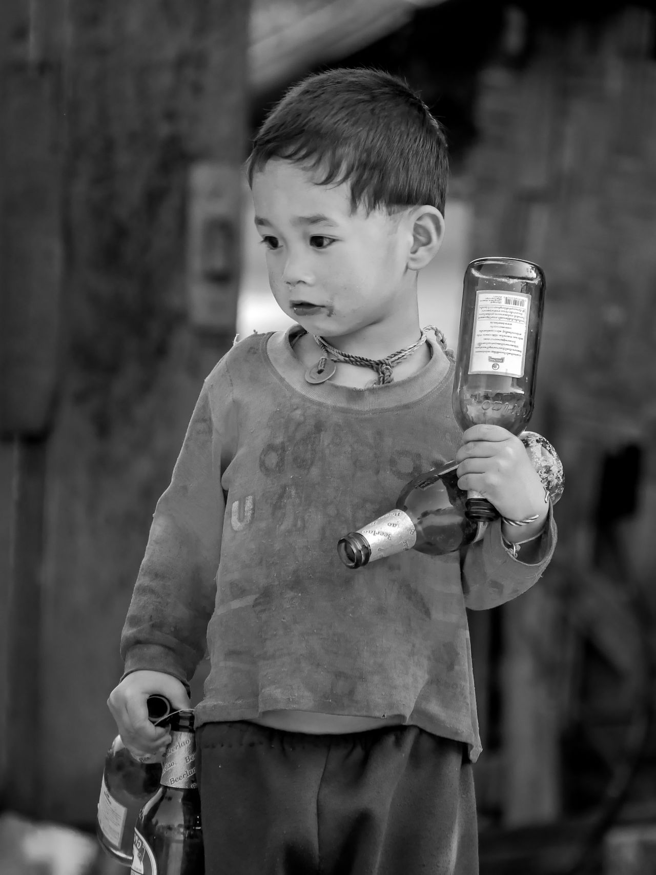 Beer Bottles Beer Lao Black & White Black And White Blackandwhite Childhood Children With Beer Elementary Age Facial Expression Focus On Foreground Front View Holding Laos Laos Village Person Standing Street Photography Streetphotography Travel Traveling Vacations