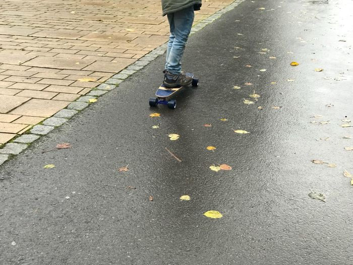 Skater boy Rain Boy Child Low Section Human Leg Real People Street Day Outdoors One Person Skateboard Shoe Lifestyles People Human Body Part
