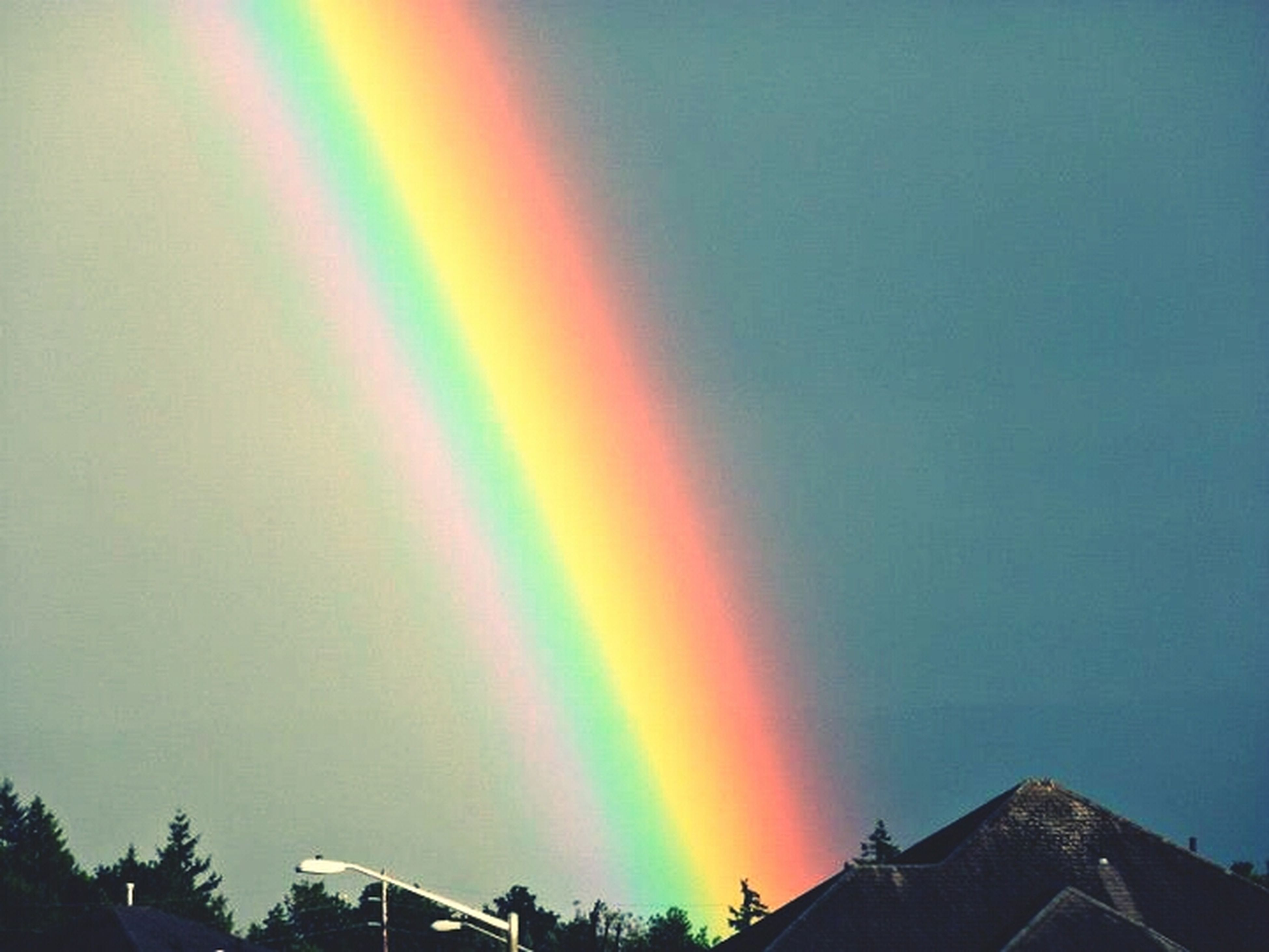 rainbow, multi colored, sky, low angle view, scenics, beauty in nature, nature, copy space, tranquility, architecture, built structure, outdoors, building exterior, no people, tranquil scene, idyllic, cloud - sky, weather, sunset, mountain