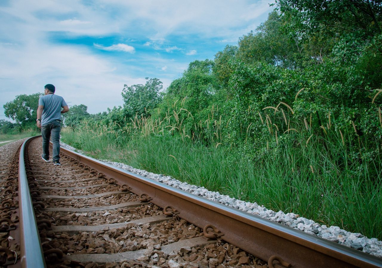 Miles Away Rear View Full Length Railroad Track One Person Rail Transportation Nature Men Real People Tree Day Outdoors Beauty In Nature Sky