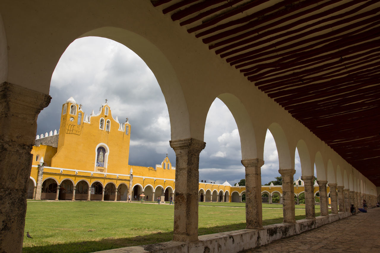 Looking throught the arches in Izamal, Mexico Ancient Arch Architectural Column Architecture Built Structure Church Cloud - Sky Colonial Day Grass History Iglesia Izamal Izamal Yucatan Mexican Church No People Travel Destinations Yellow Yellow City Yucatan Mexico Yúcatan