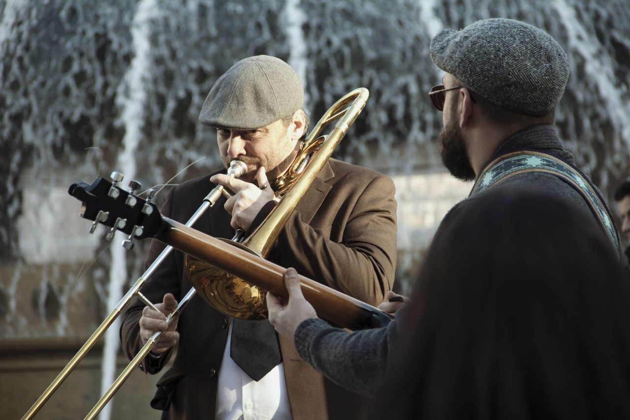 two people, music, young men, holding, playing, concentration, men, musical instrument, real people, young adult, musician, performance, standing, outdoors, togetherness, weapon, day, wind instrument, adult, people