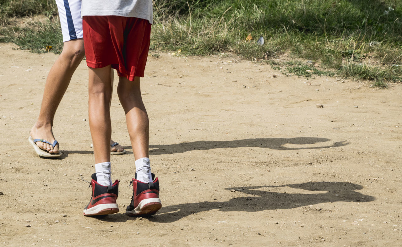 low section, human leg, standing, shorts, shoe, leisure activity, one person, real people, outdoors, lifestyles, day, shadow, sport, young adult, soccer shoe, adult, adults only, people