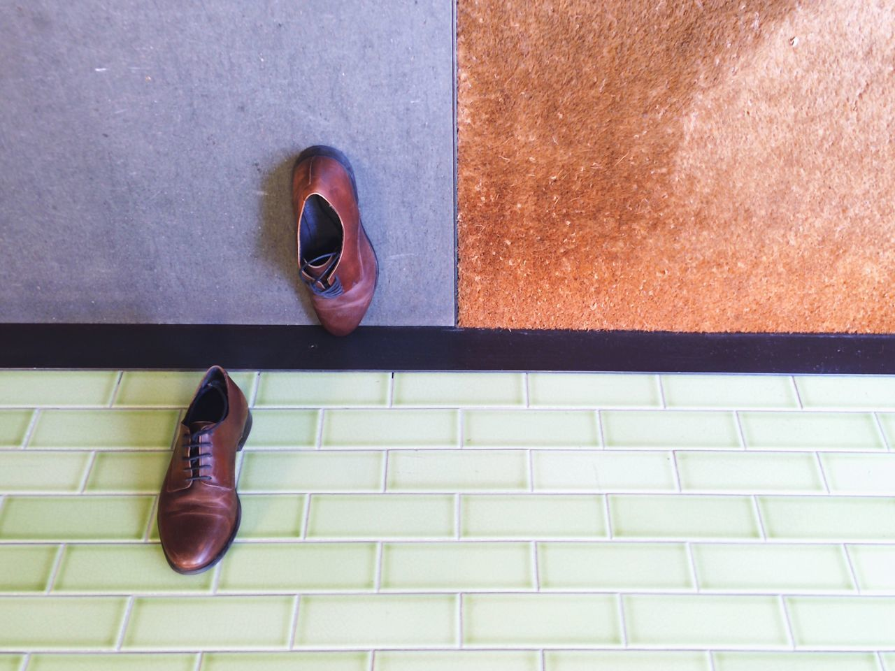 Close-Up High Angle View Of Shoes On Tiled Floor